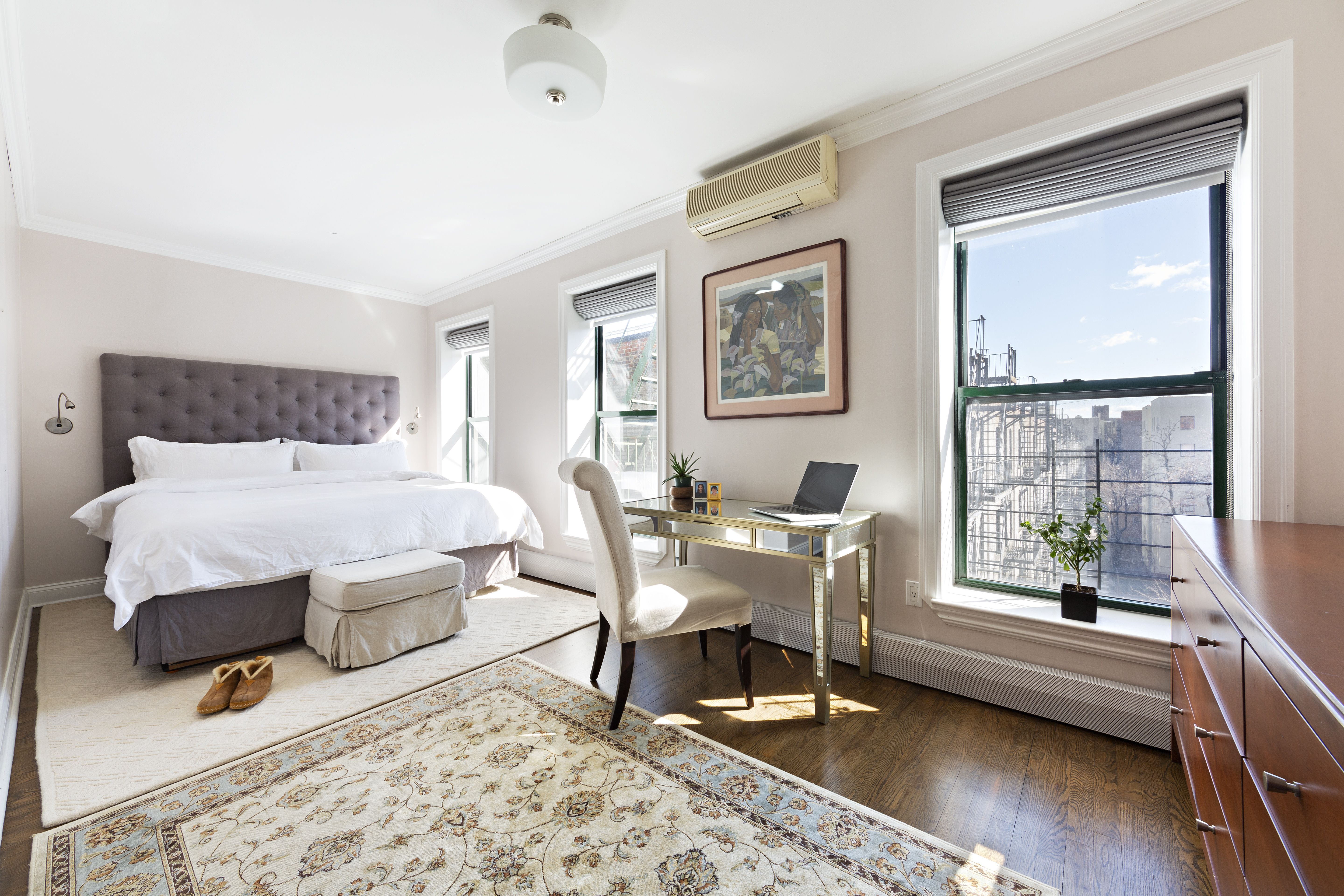 A bedroom with three floor-to-ceiling windows, hardwood floors, a large bed, and a rug.