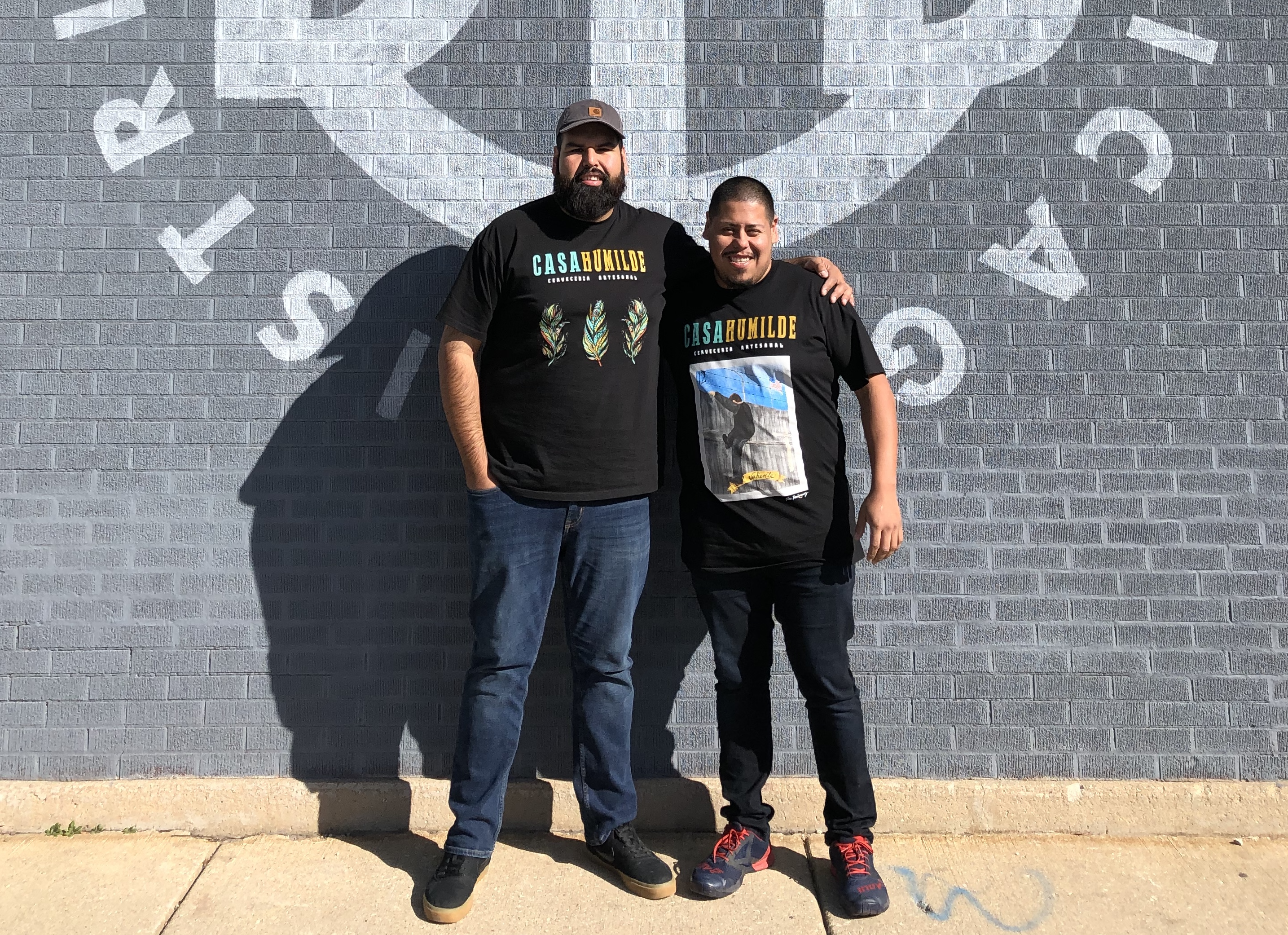 A pair of brothers posing together in front of a brick wall.