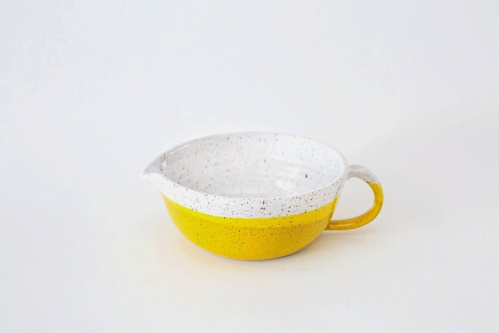 A yellow and white ceramic bowl with a spout and handle