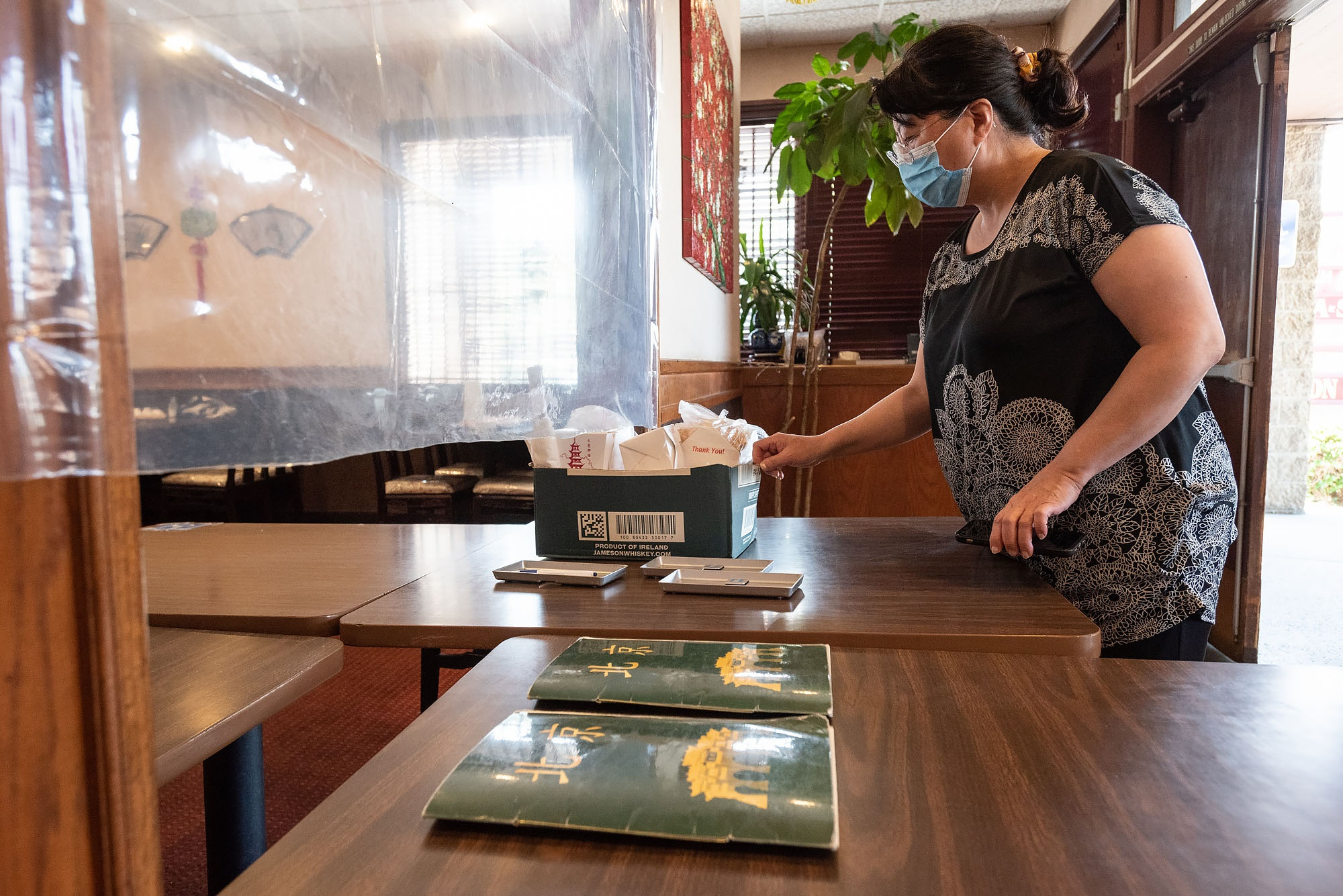 Customer picks up a takeout order at Peking Gourmet in Garden Grove's Koreatown