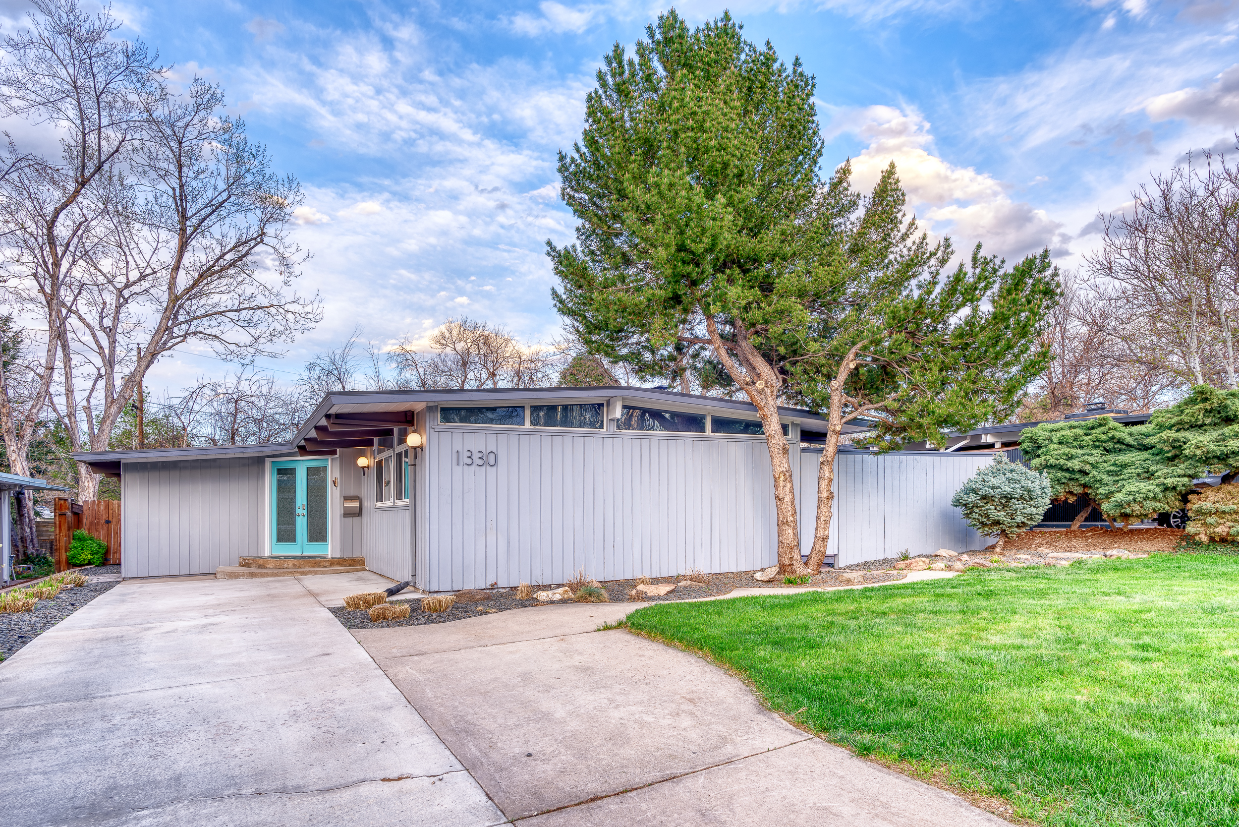 An exterior view of a gray midcentury modern house. There is a driveway, green grass, and a tree.