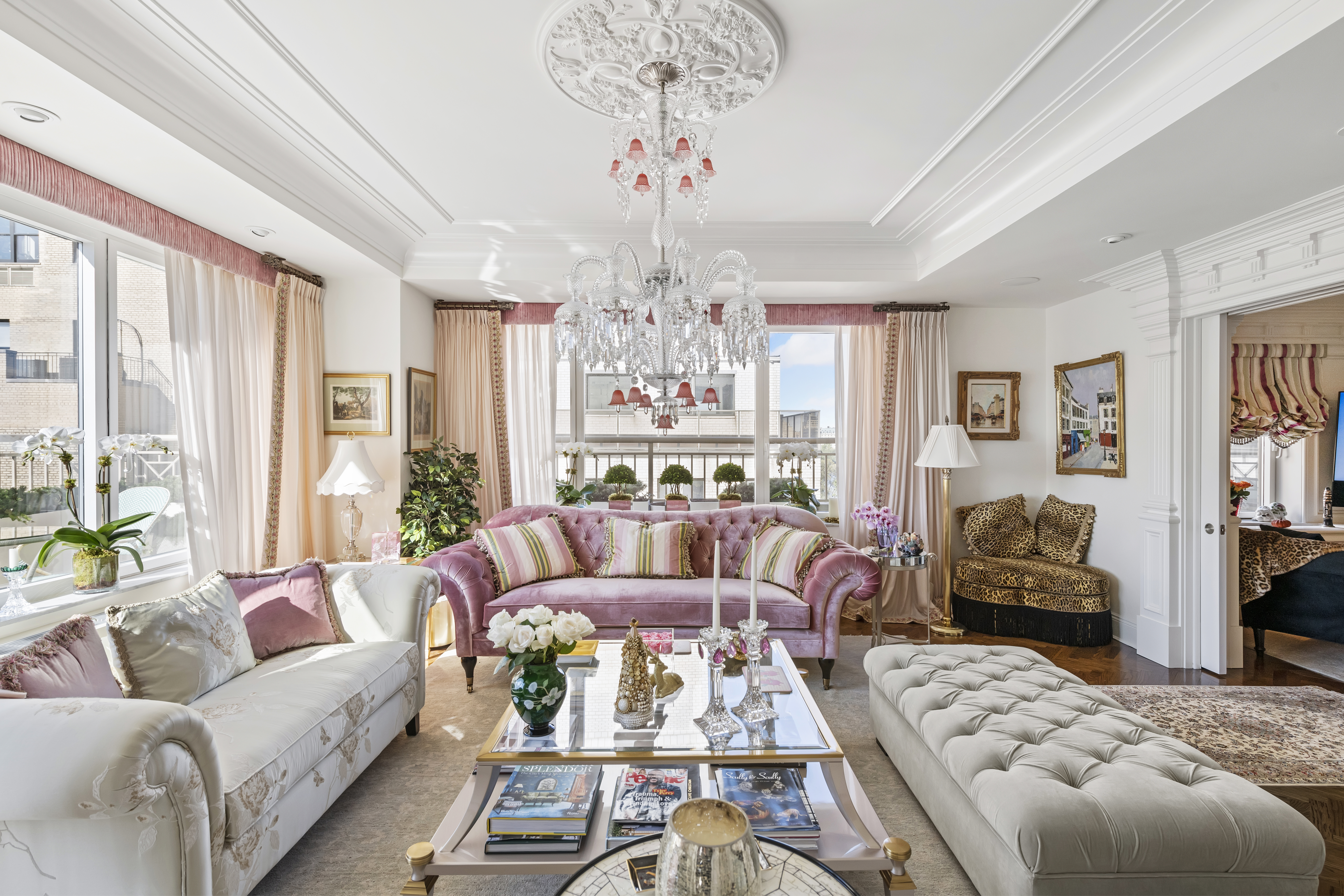 A living room with a chandelier, a pink couch, and a glass coffee table.