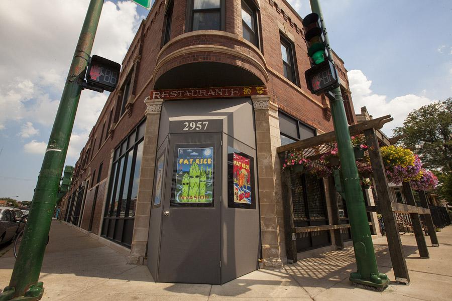 The exterior of a restaurant's door, between two traffic light posts.