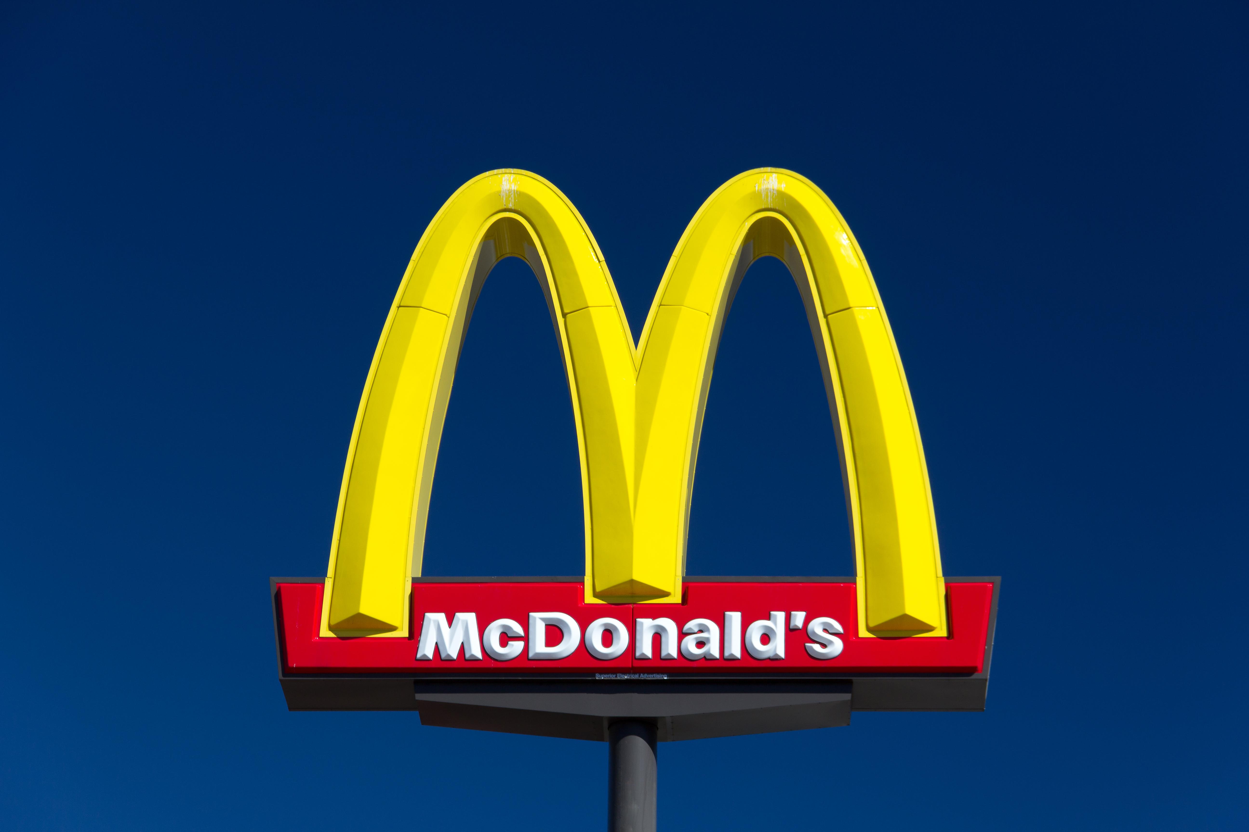 A McDonald's restaurant sign on a blue sky background.