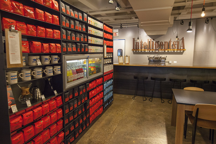 A coffee shop bar and a shelf on the left full of coffee bags.