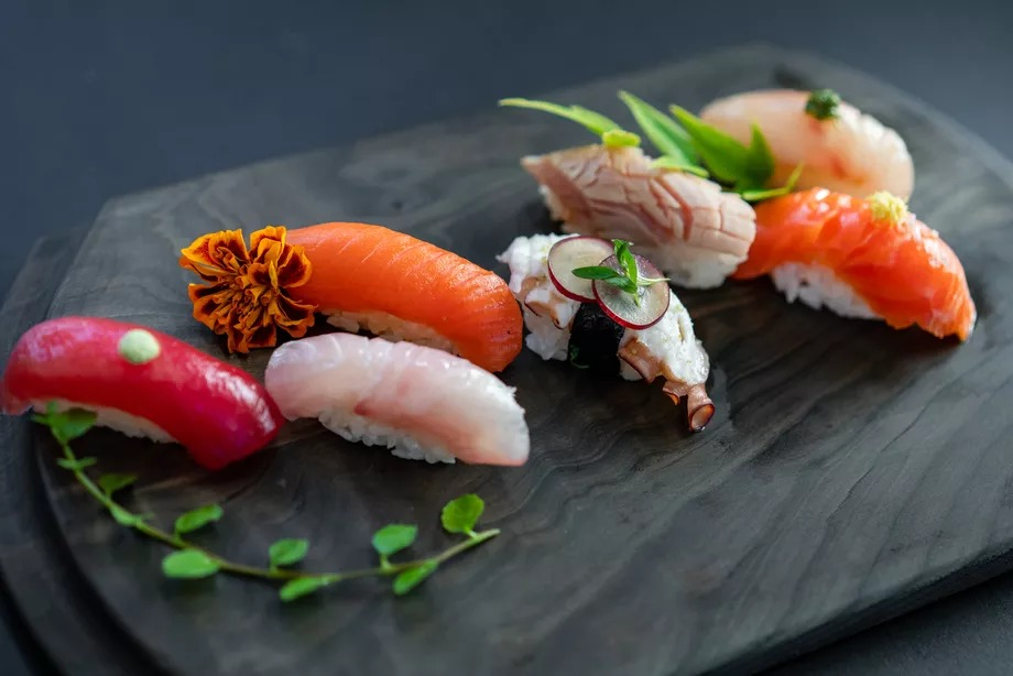 A dark gray stone platter holds seven pieces of fish-topped nigiri, ranging from purple tuna to a puckered chunk of octopus tentacle.