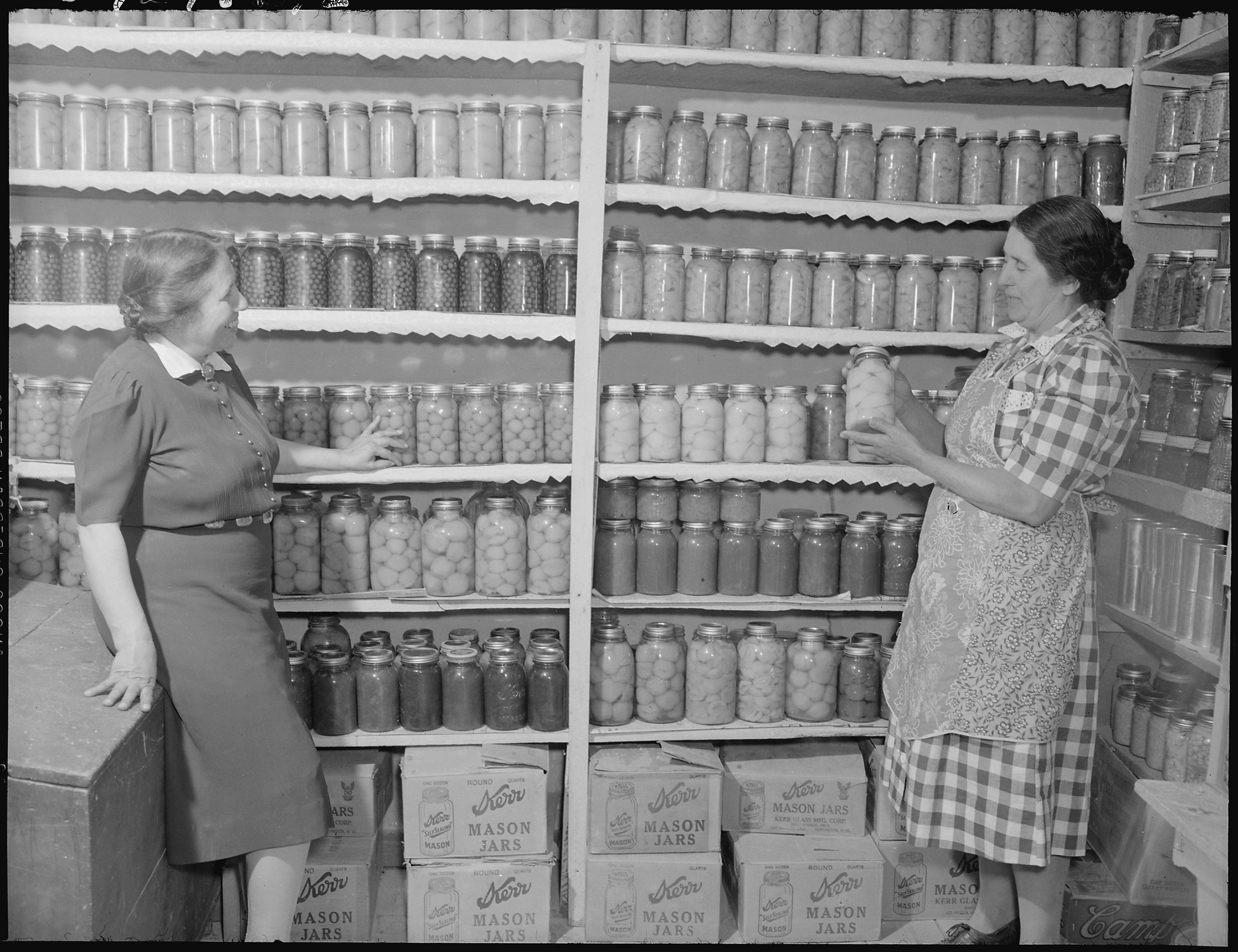 Two women stand by shelves stocked with jars