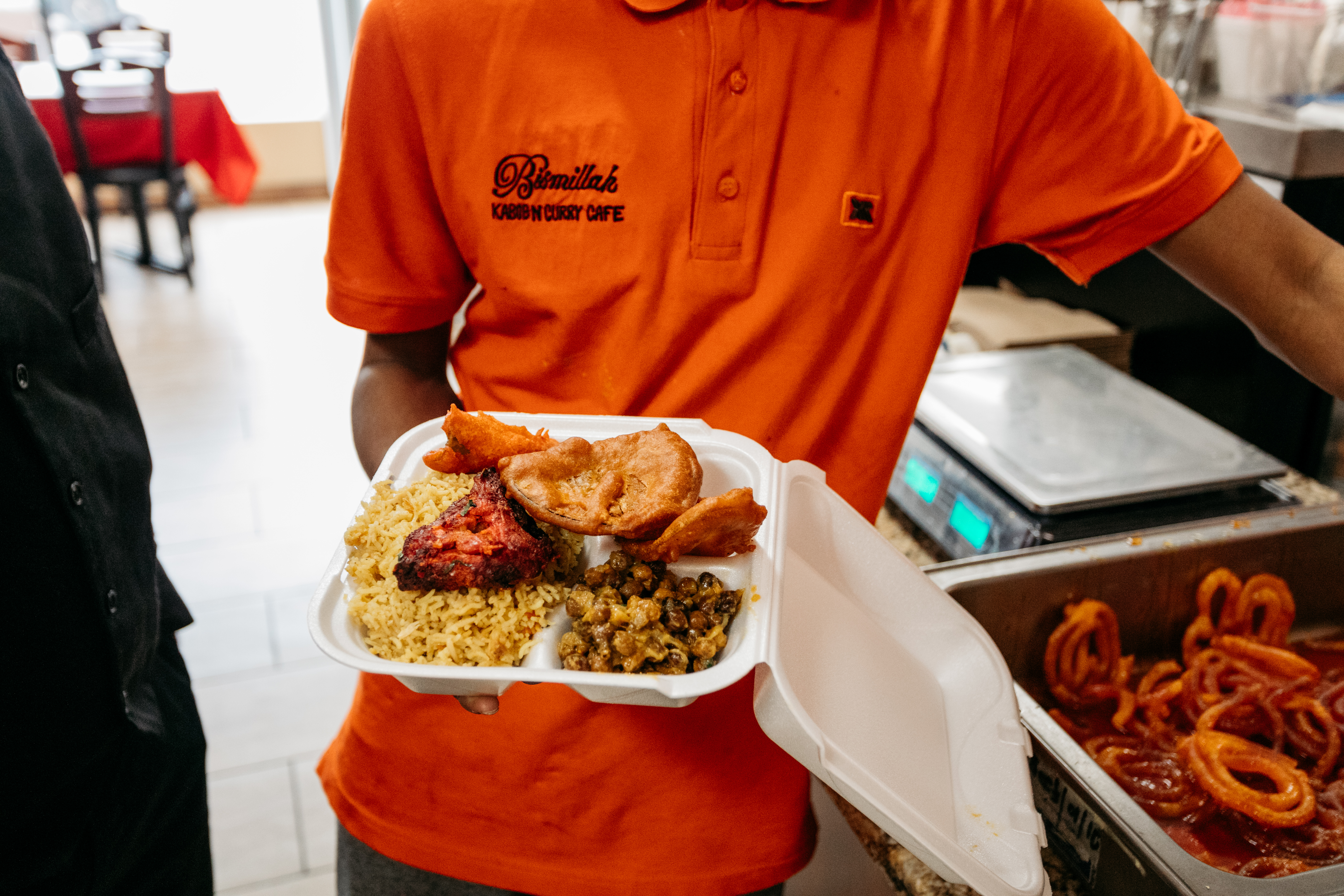 An employee at Bismillah Kabob in an orange work shirt fills a carryout container with items for an iftar box.