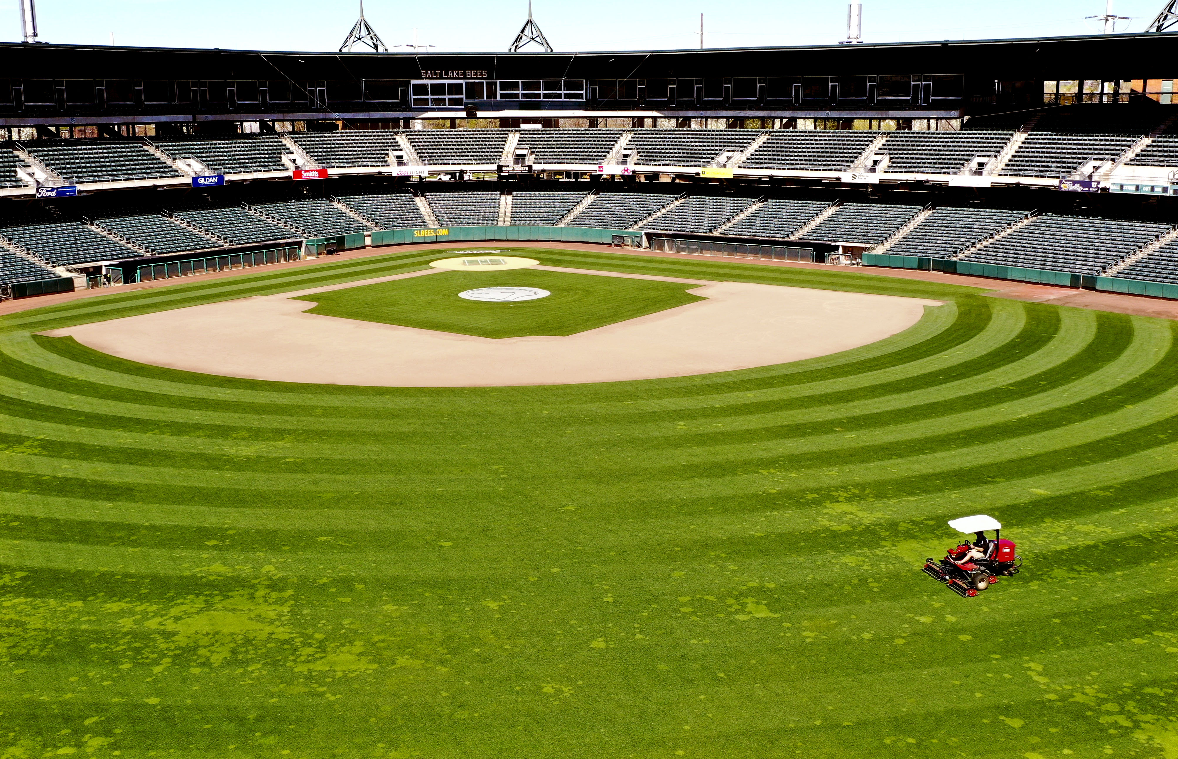 Brian Soukup, director of field operations for the Salt Lake Bees, mows the field at Smith's Ballpark in Salt Lake City on Wednesday, April 8, 2020. Soukup is intentionally keeping the discolored grass in an effort to save money until the season begins.