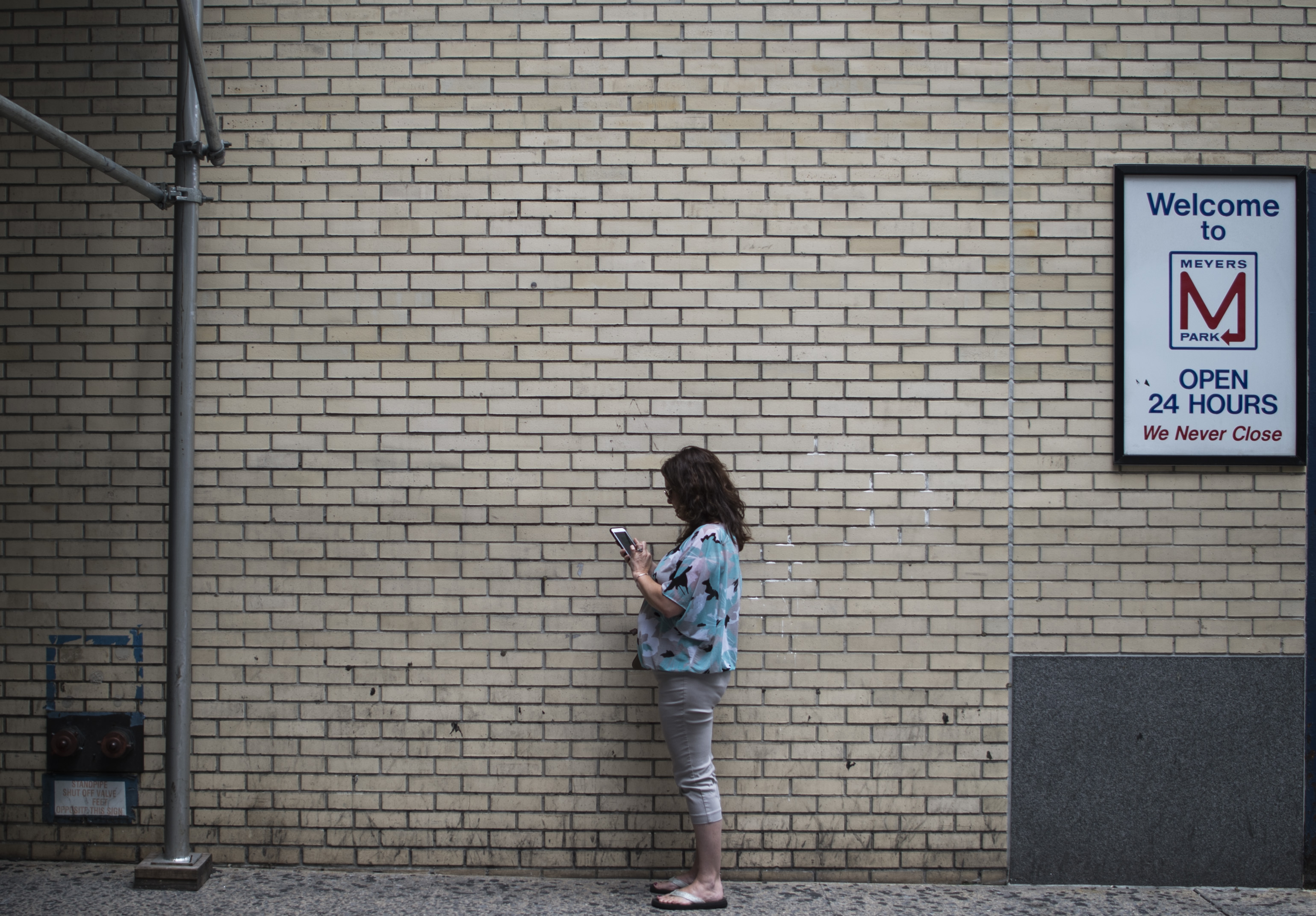 A woman looks at a phone near a wall.