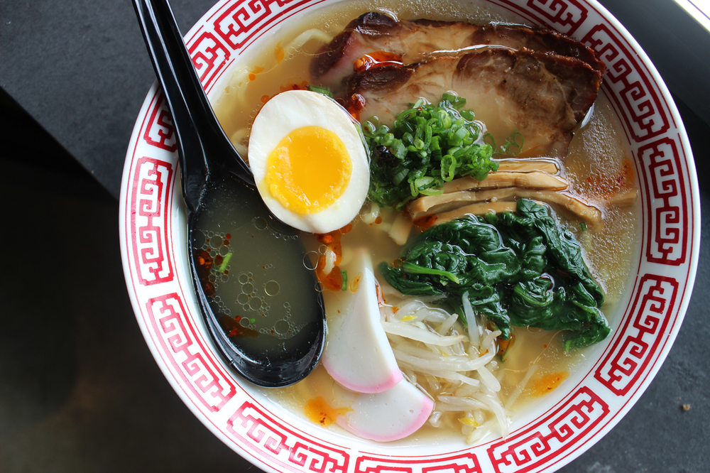 A bowl of ramen comes with a half of a boiled egg, mushrooms, and spinach, with a golden yellow broth