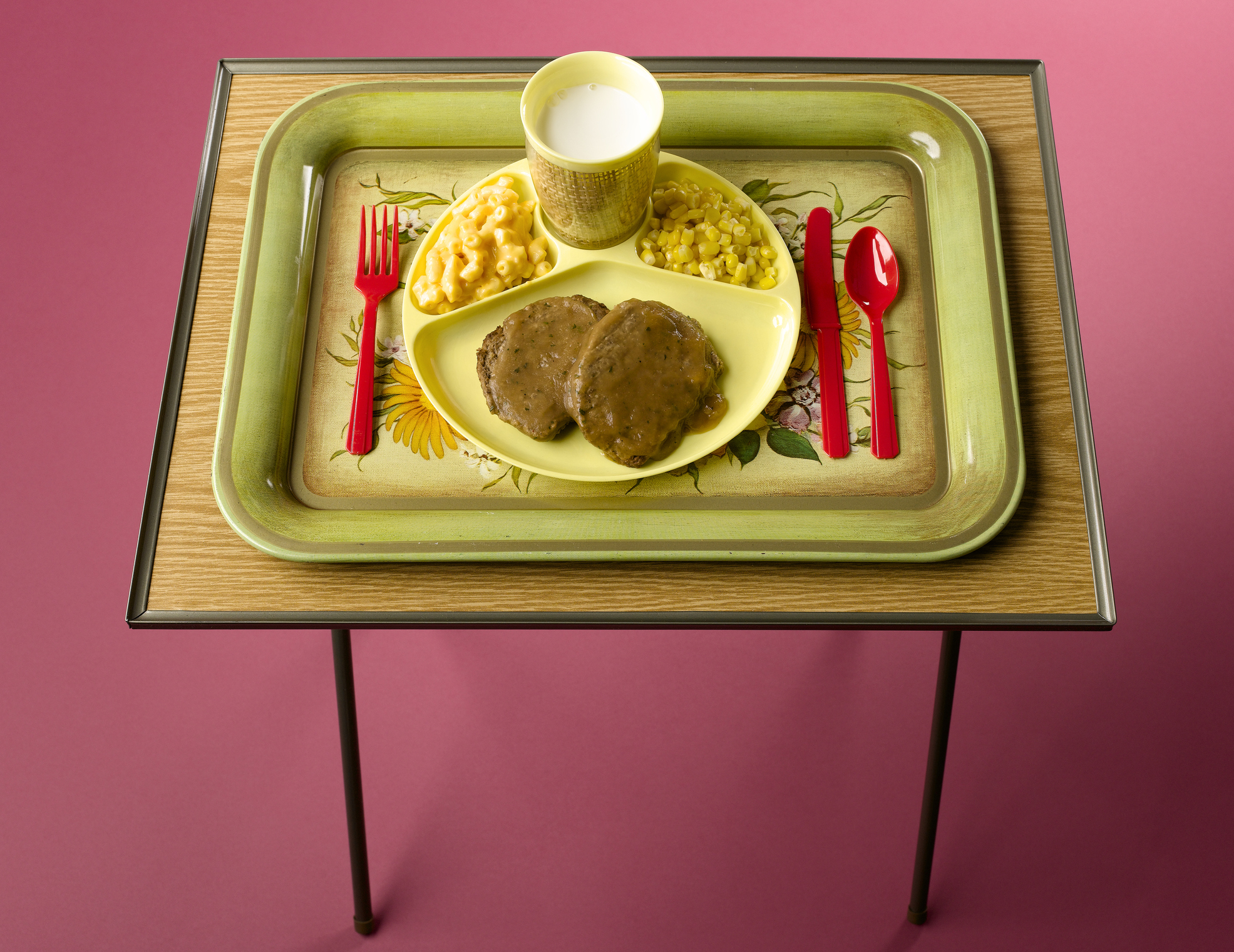 a divided plate with food sits on a tv tray.