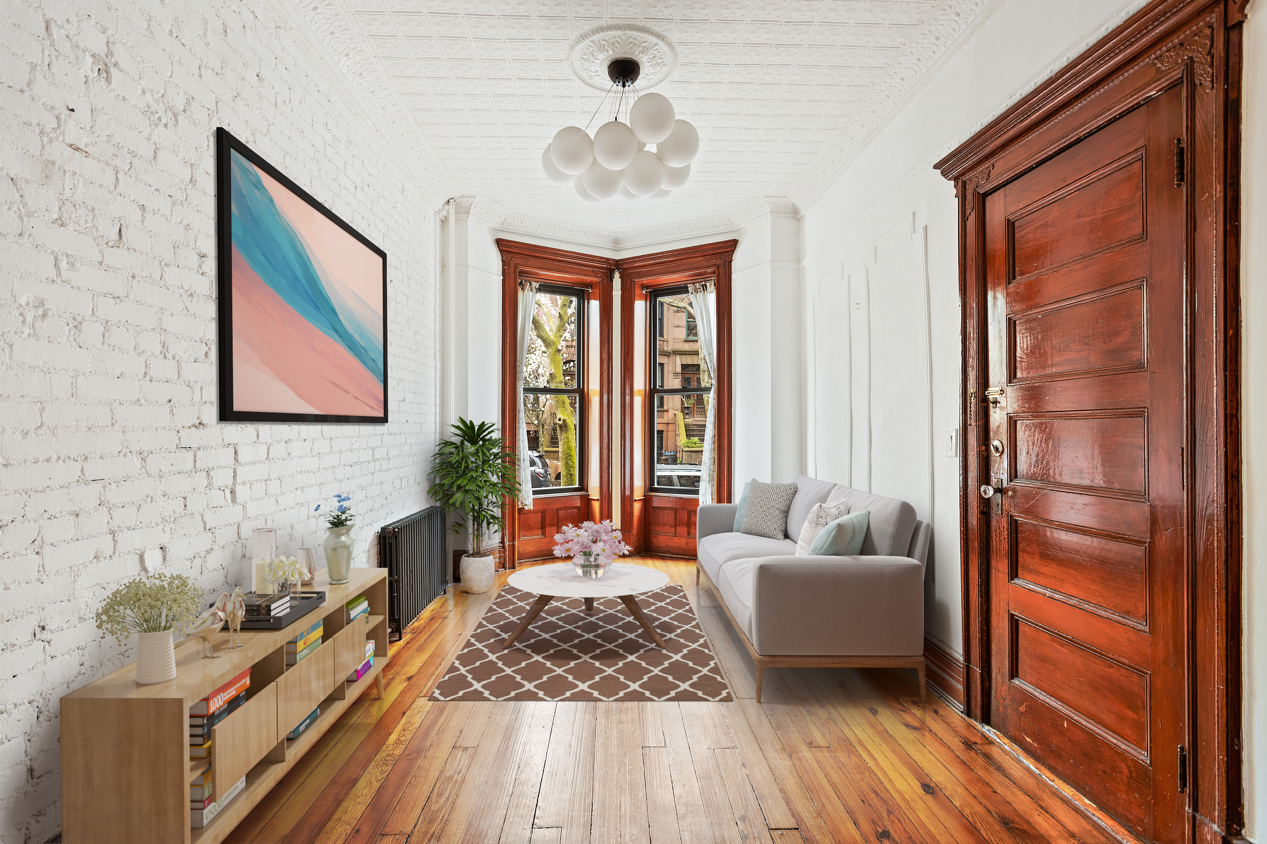 A living area with white exposed brick, hardwood floors, and bay windows.