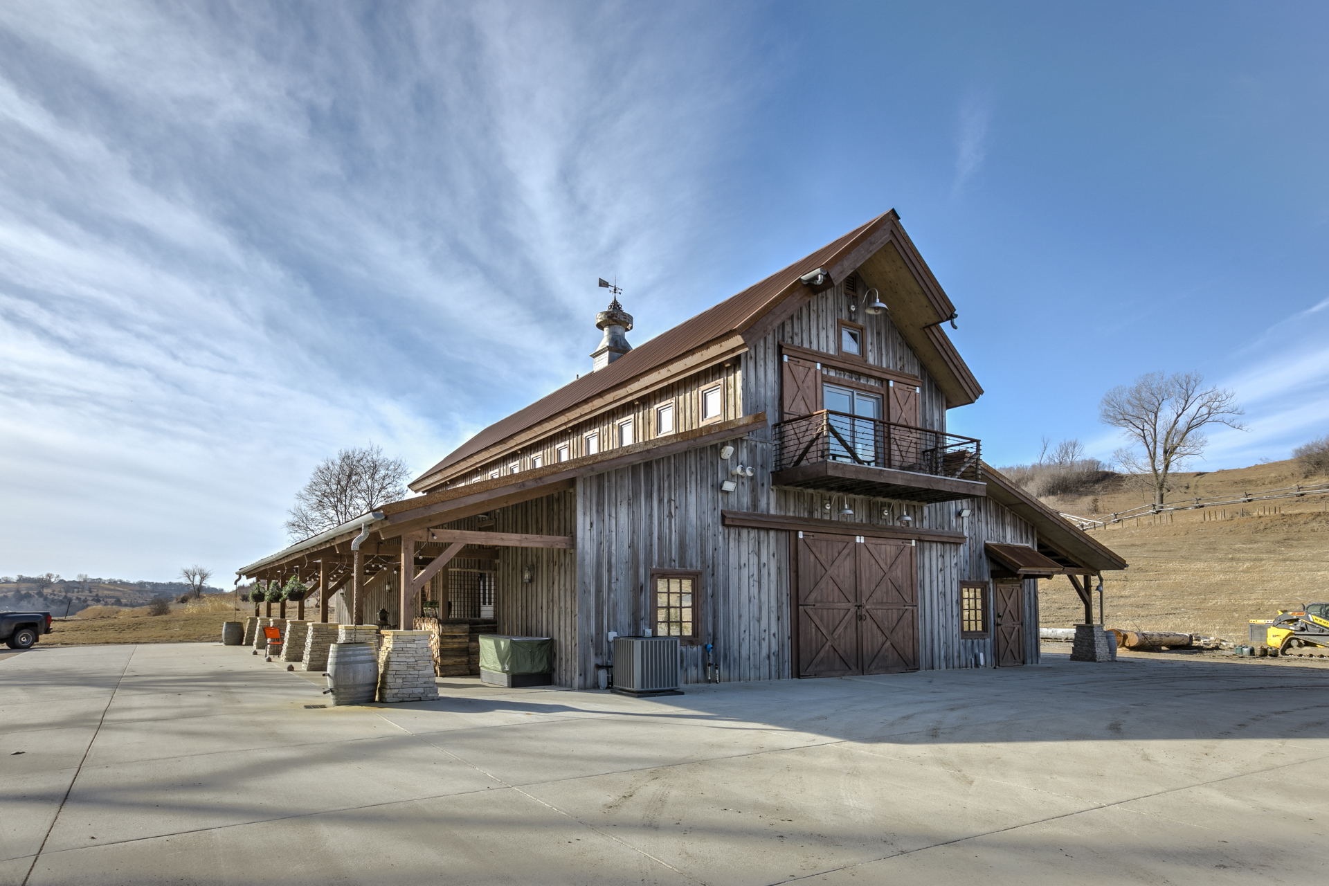 An exterior view of a barn house with a wood facade and a large steel sliding door.