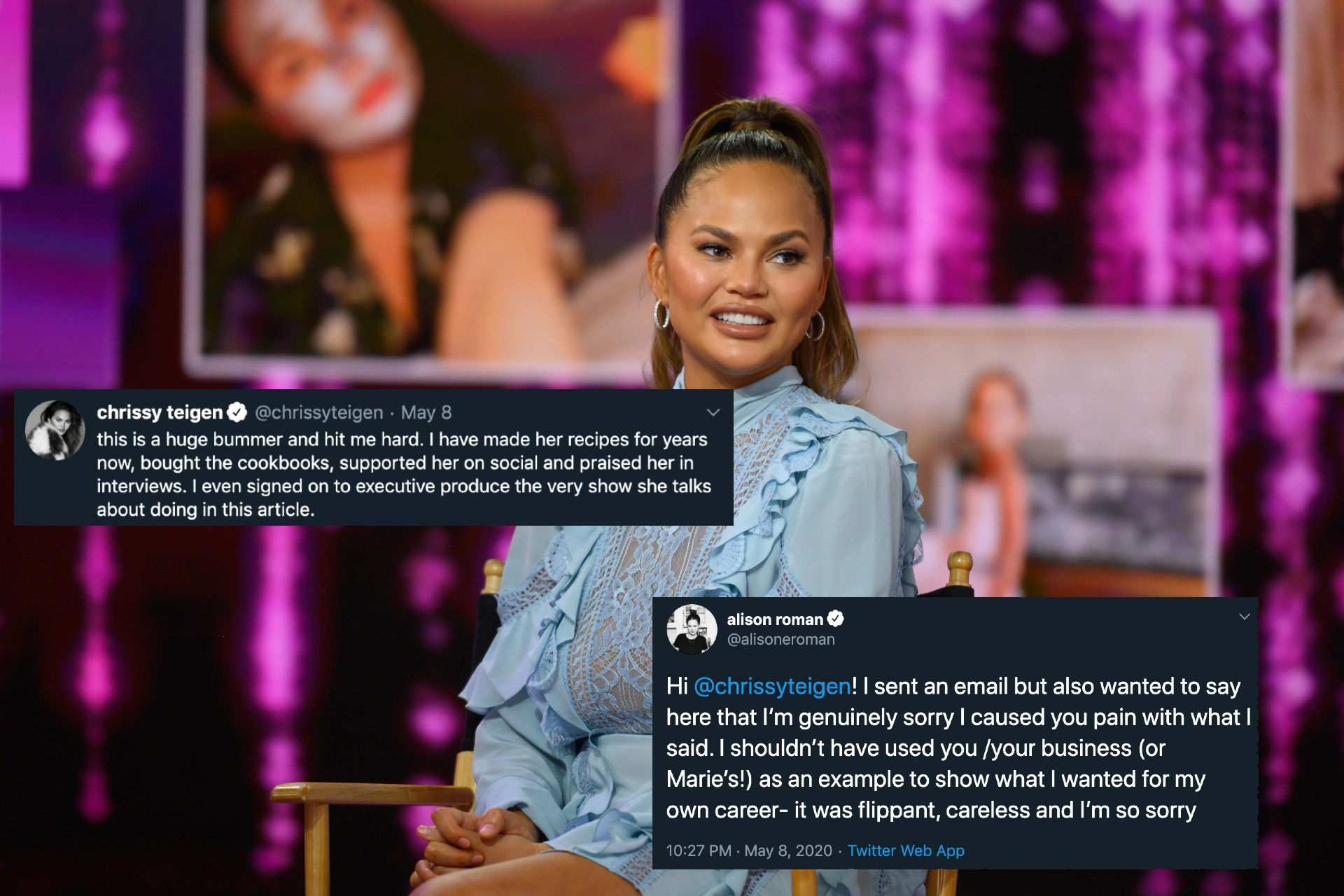 Chrissy Teigen, wearing a light blue dress and her hair in a high ponytail, sits on a folding chair onstage in front of a shiny purple backdrop.