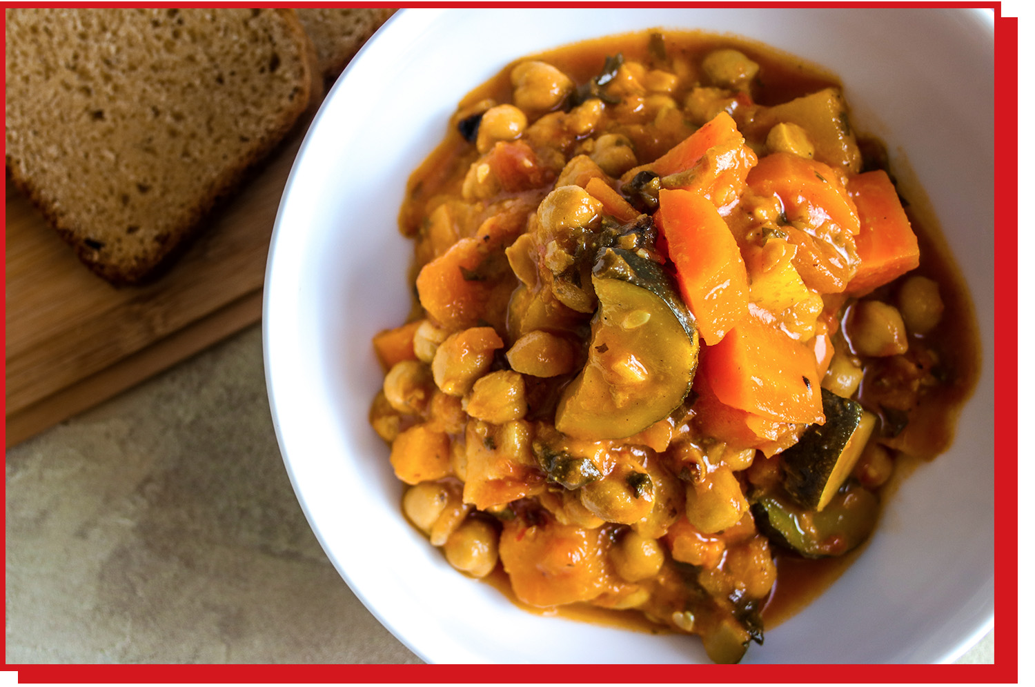 Bowl of chickpea and sweet potato stew in a white bowl.