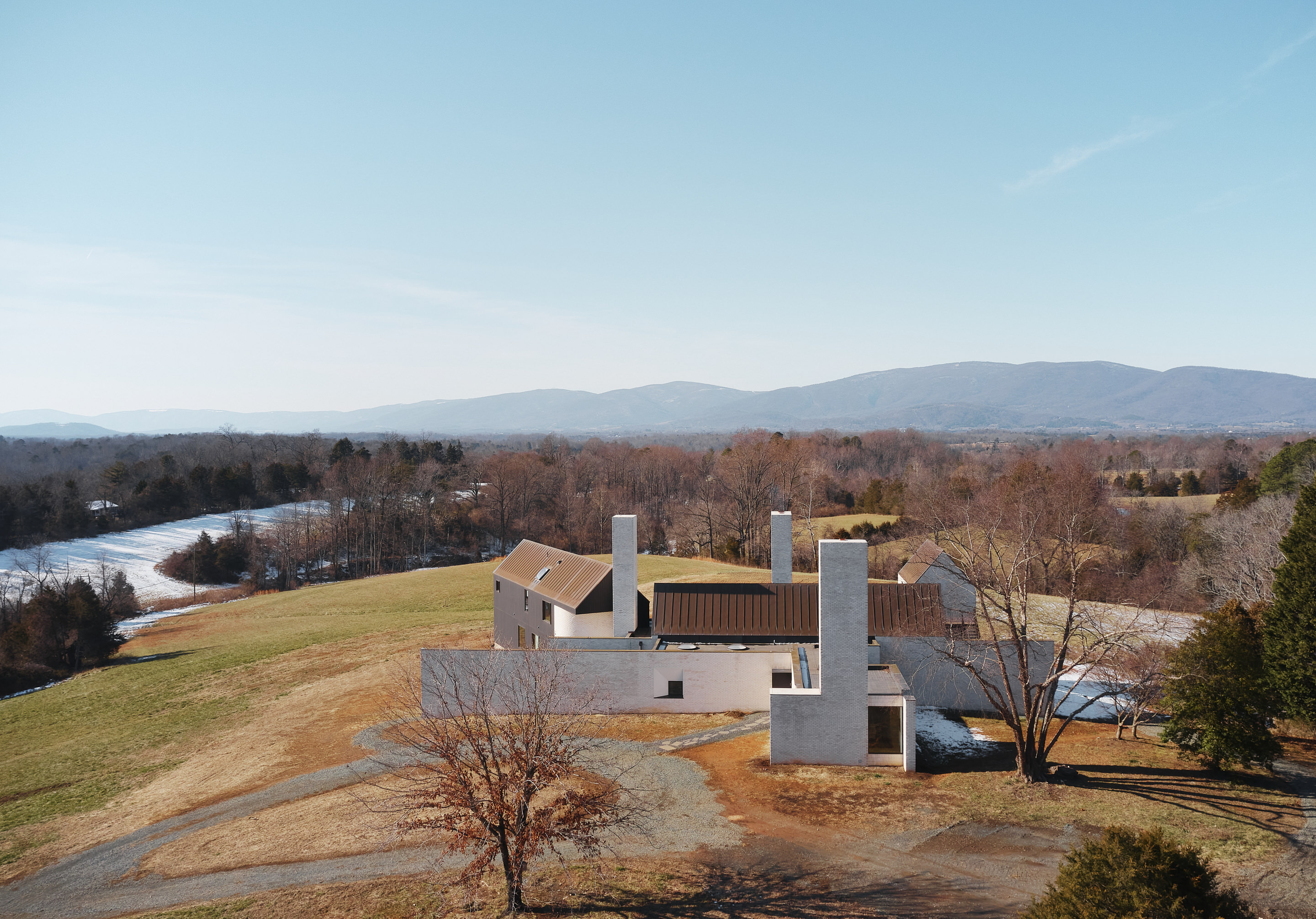 Aerial view of house with three chimneys.