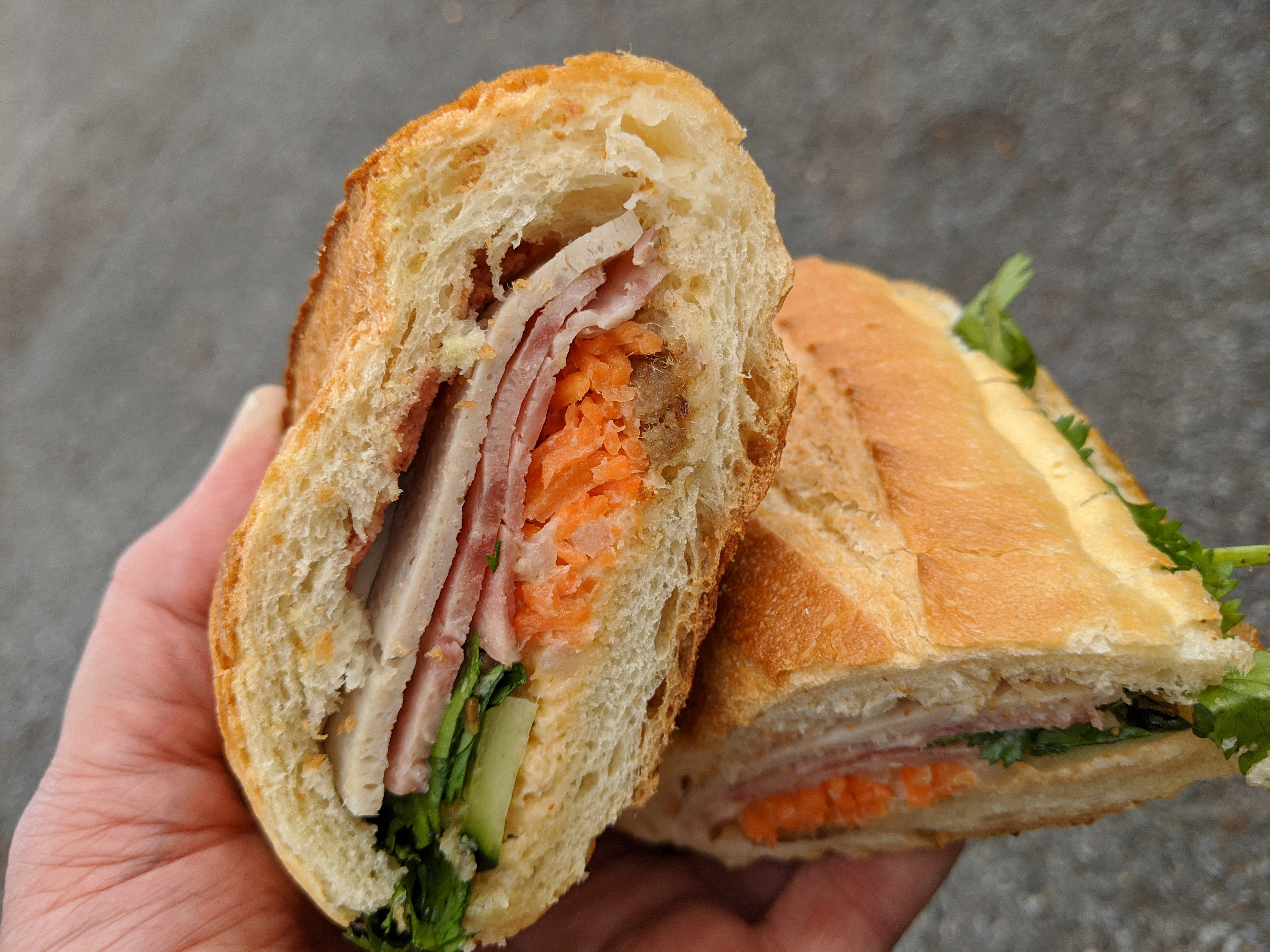 A baguette sandwich cut in half to reveal layers of meat and vegetables.