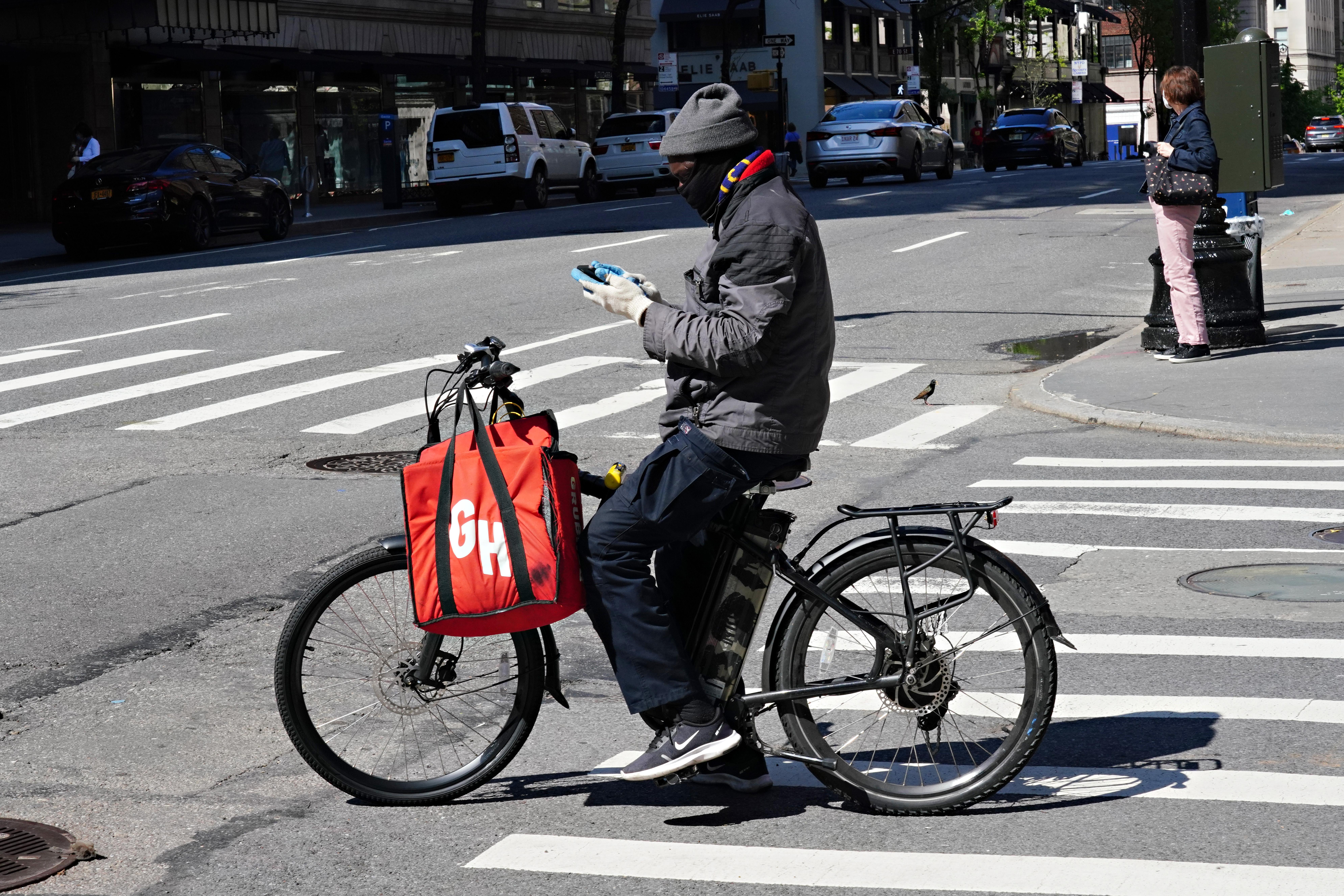 Man on bike wearing face mask checks phone, a Grubhub bag is hanging from the handlebars.
