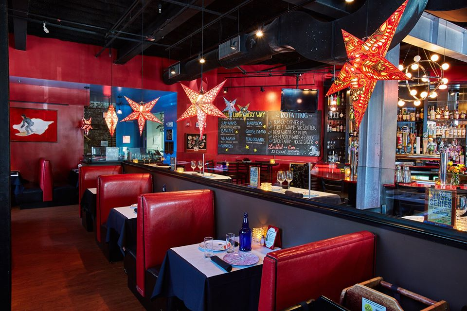Interior restaurant and bar photo with red walls, shiny red booths, and hanging decorative star lamps (also red).