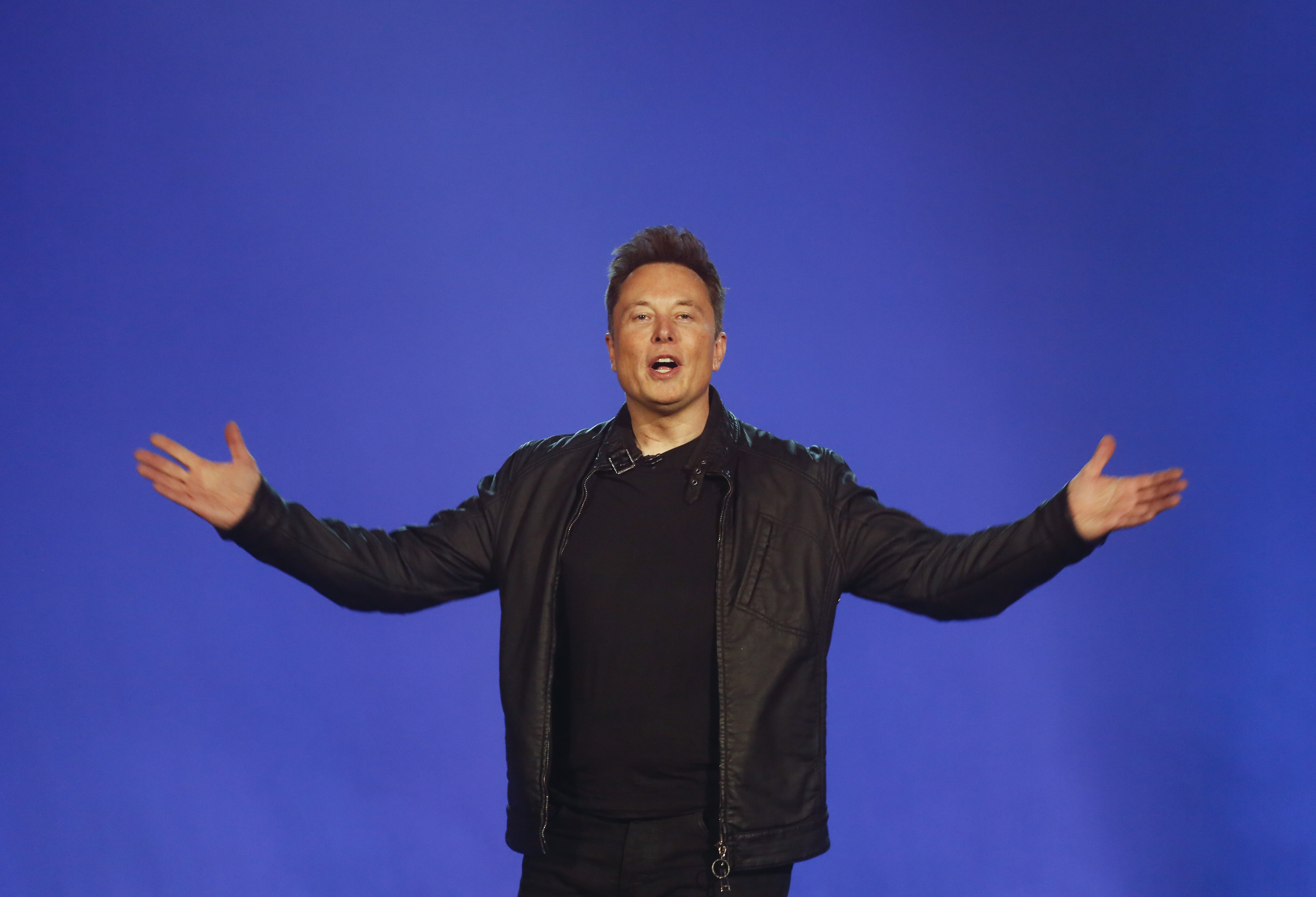 Elon Musk standing on a stage with his arms out.