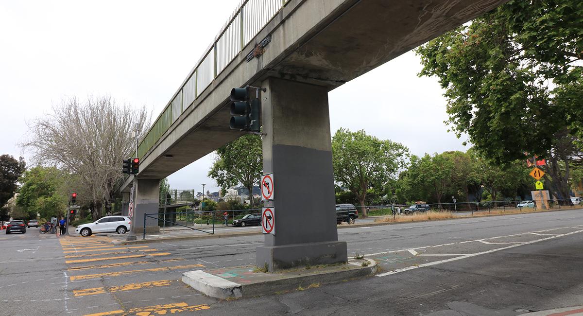 A concrete bridge over a busy street.