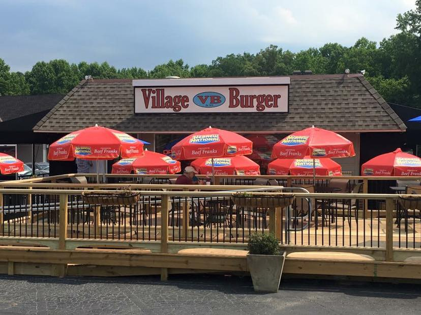Village Burger patio in Dunwoody Village with umbrellas and tables and chairs taken in July 2019