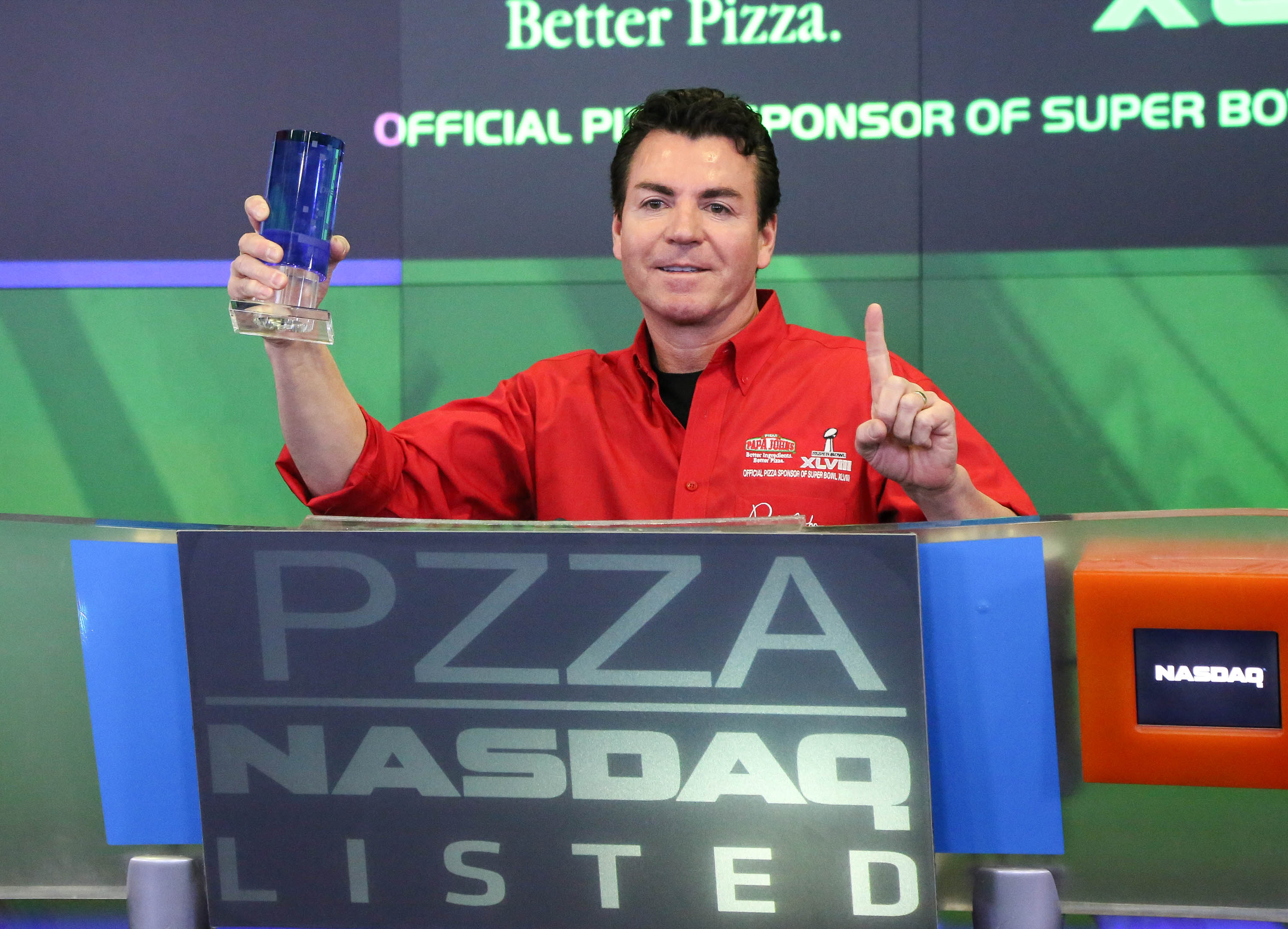 John Schnatter, formerly of Papa John's, wears a red zip-up and stands in front of blue and green graphics when ringing the opening bell at NASDAQ.