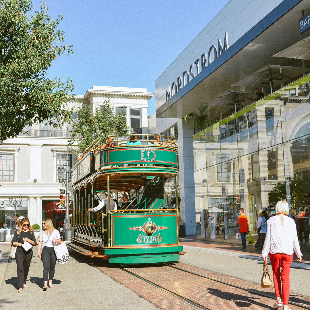 A light green trolley passed beyond customers at an upscale outdoor mall.