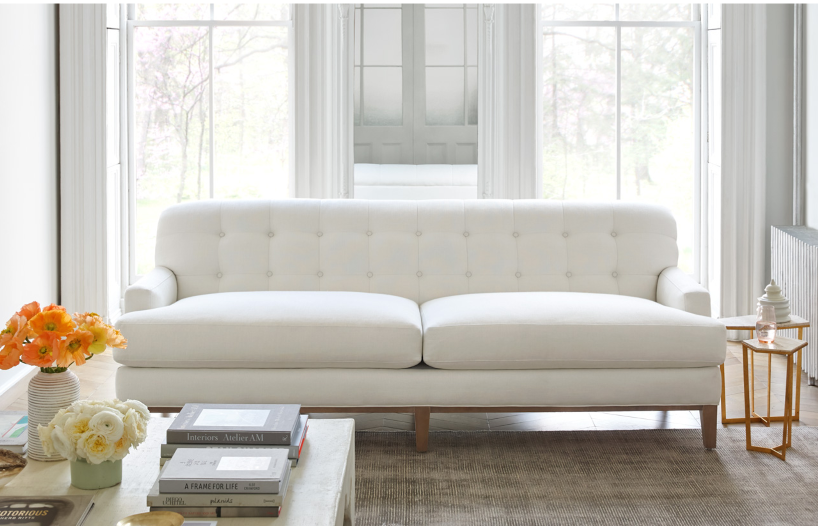 White two-seat tufted sofa.