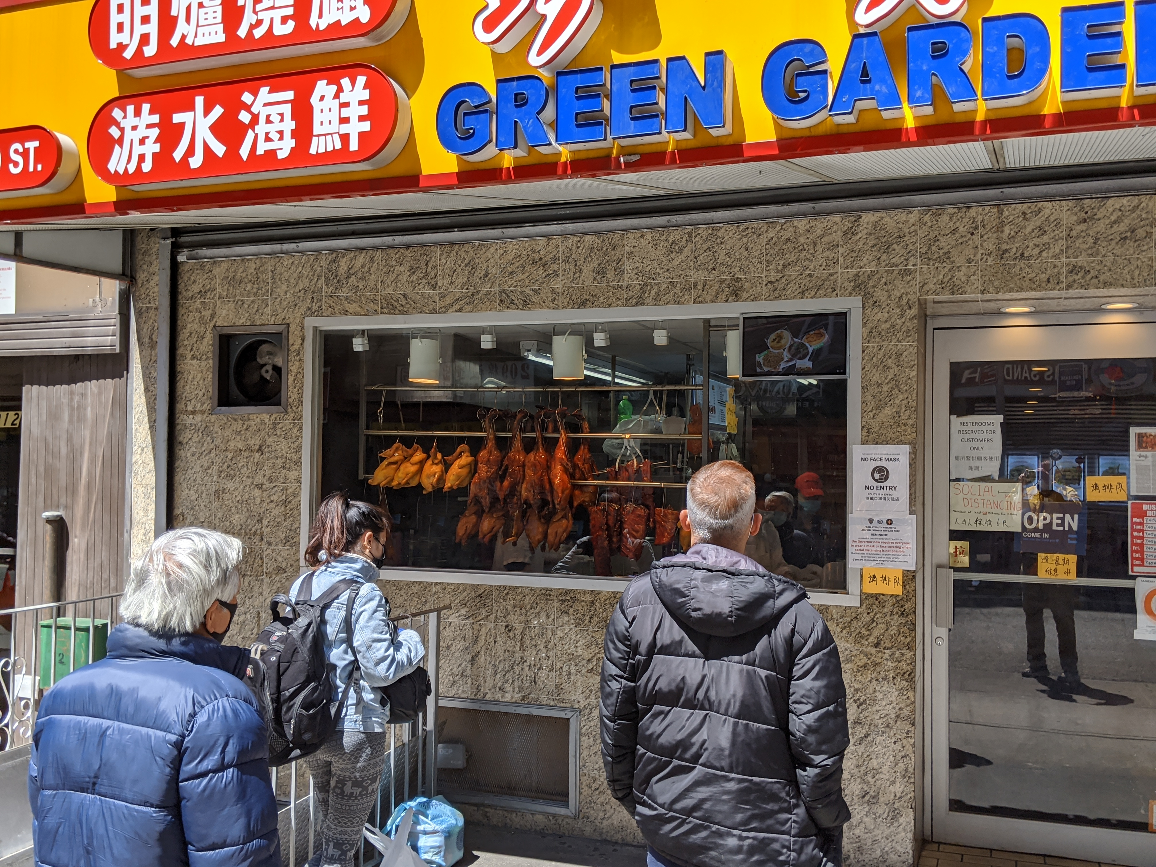 A line in front of the restaurant with ducks and pork seen in the window.