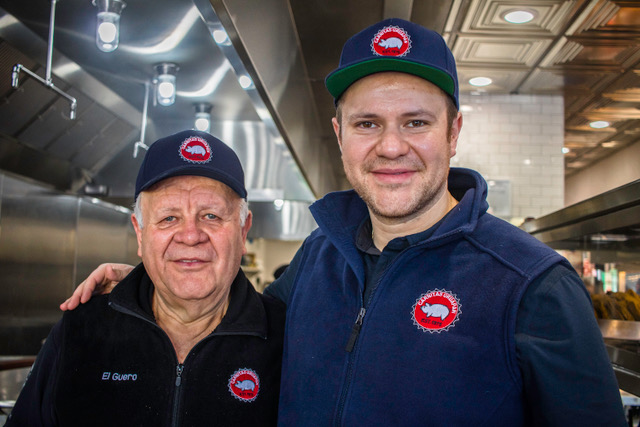 A father and son stand together inside a restaurant kitchen.