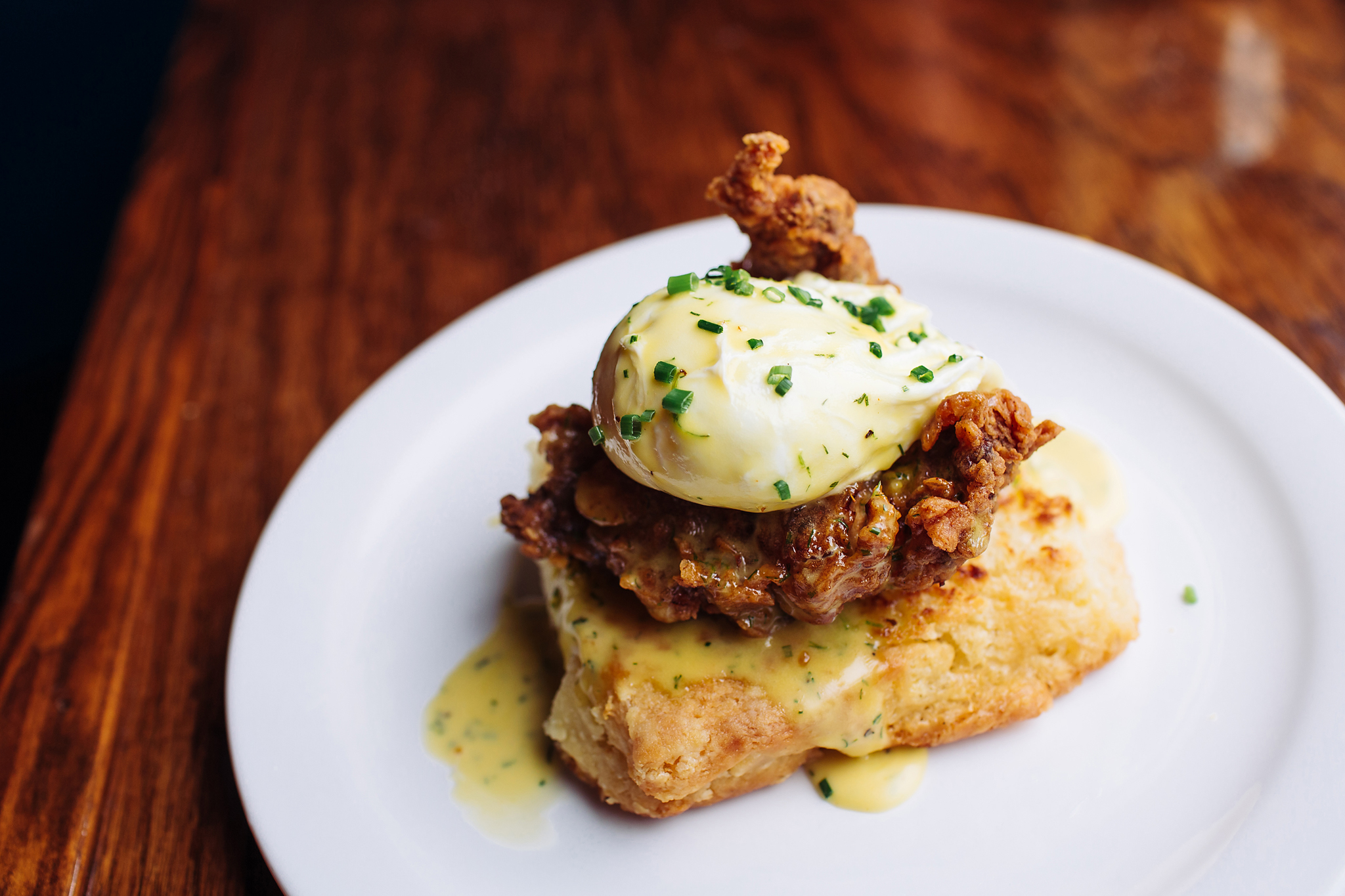 A piece of fried chicken sits on a biscuit with a poached egg perched on top at Blackheart