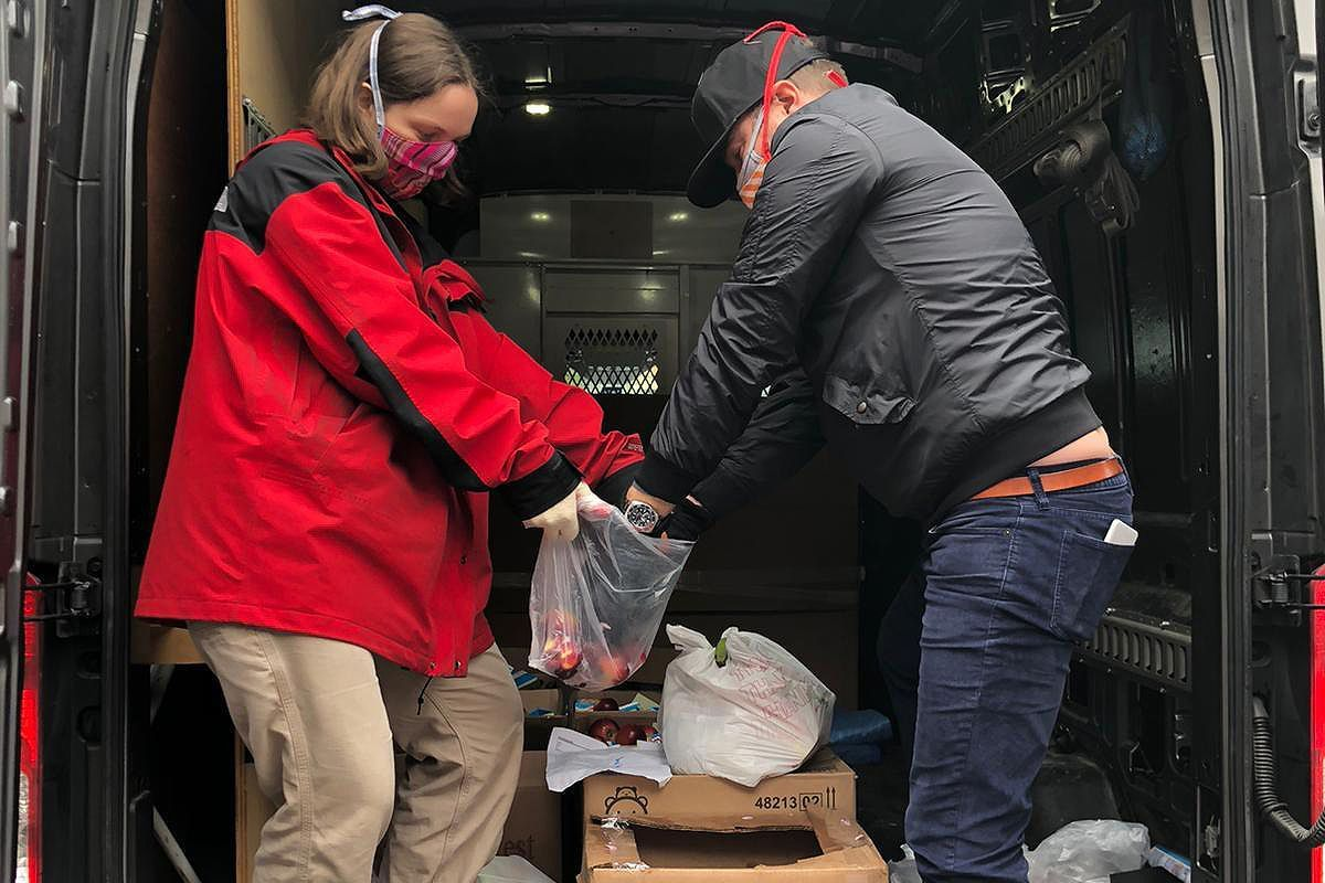 Volunteers with Astoria Mutual Aid load up a twice-weekly food distribution shuttle that takes groceries to locals who need them.