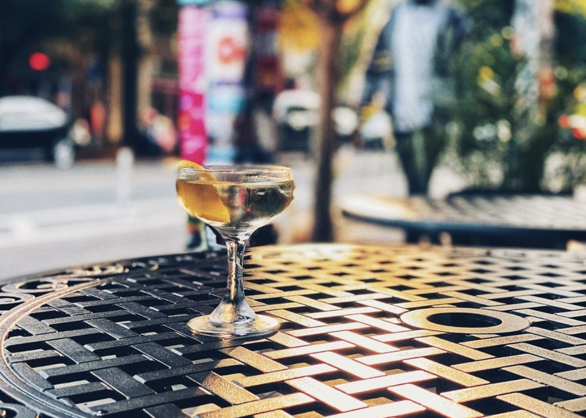A martini sits on an outdoor patio table on a sunny day.