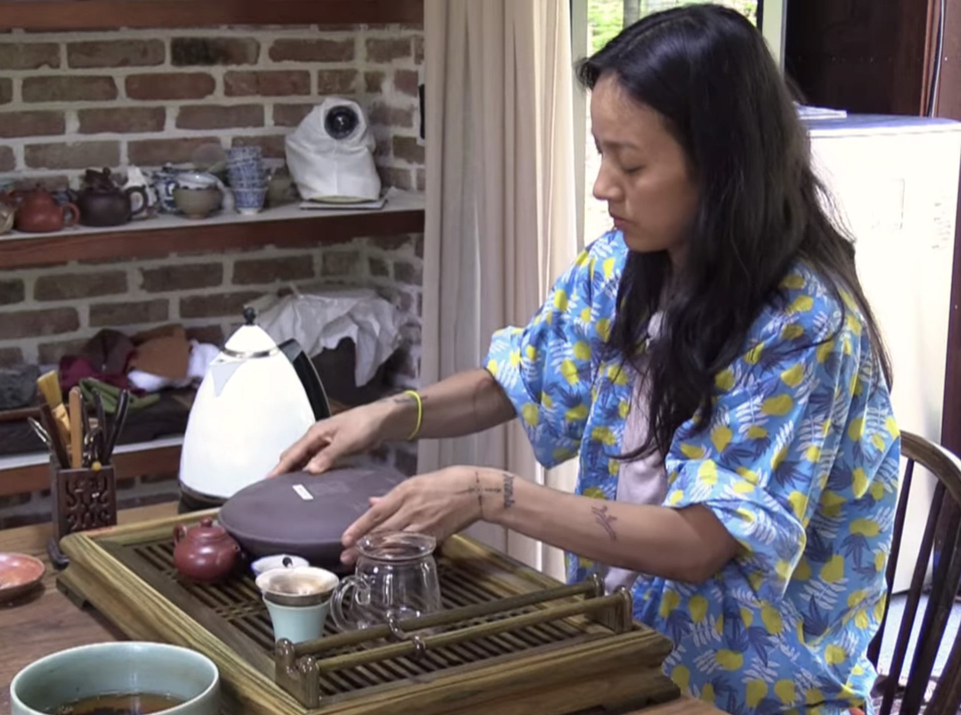 Woman in an oversized shirt sits at a table with a tea set in front of her.