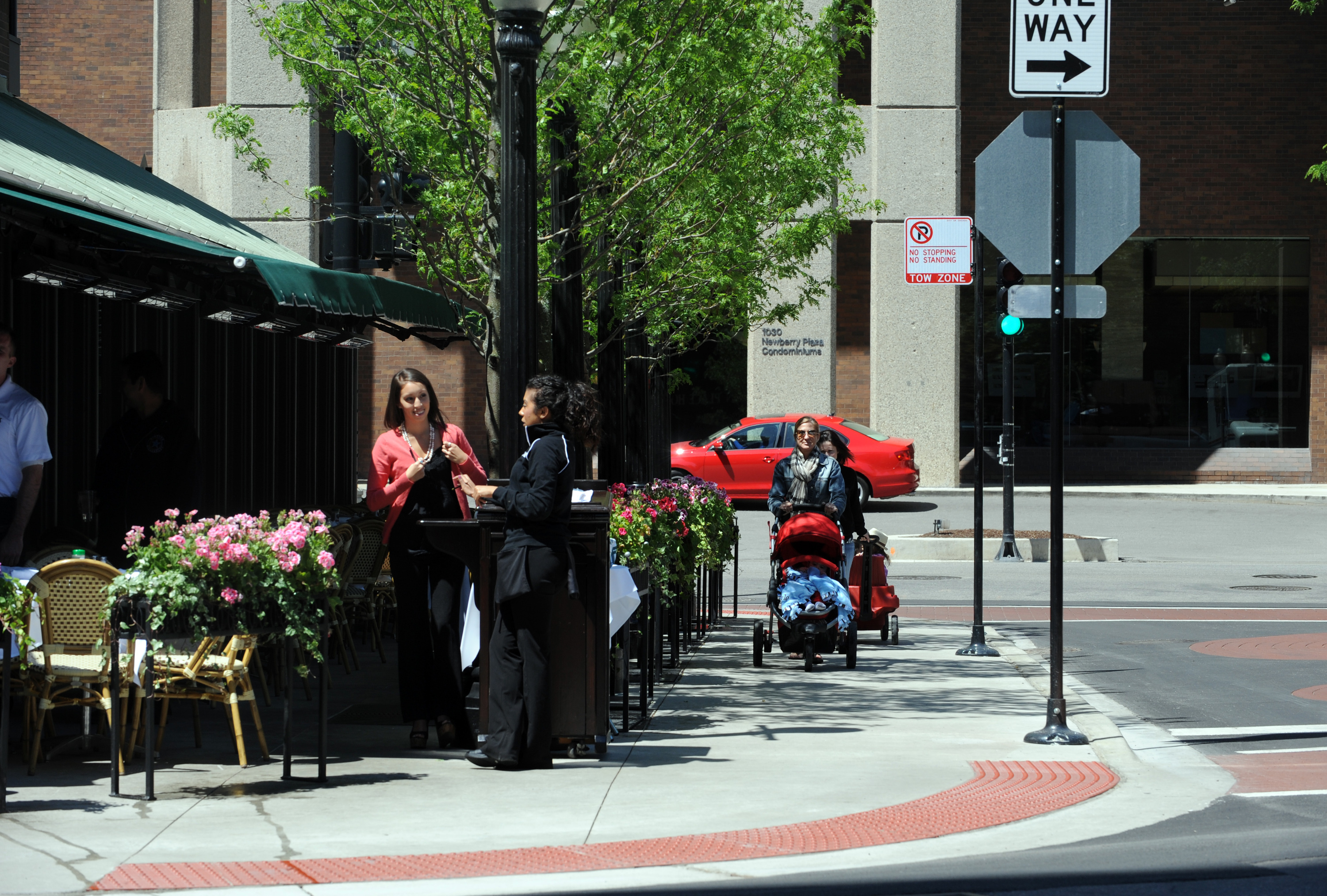 A woman pushes a stroller on a recently added sidewalk next to Gibsons Bar and Restaurant, 1028 N. Rush St.