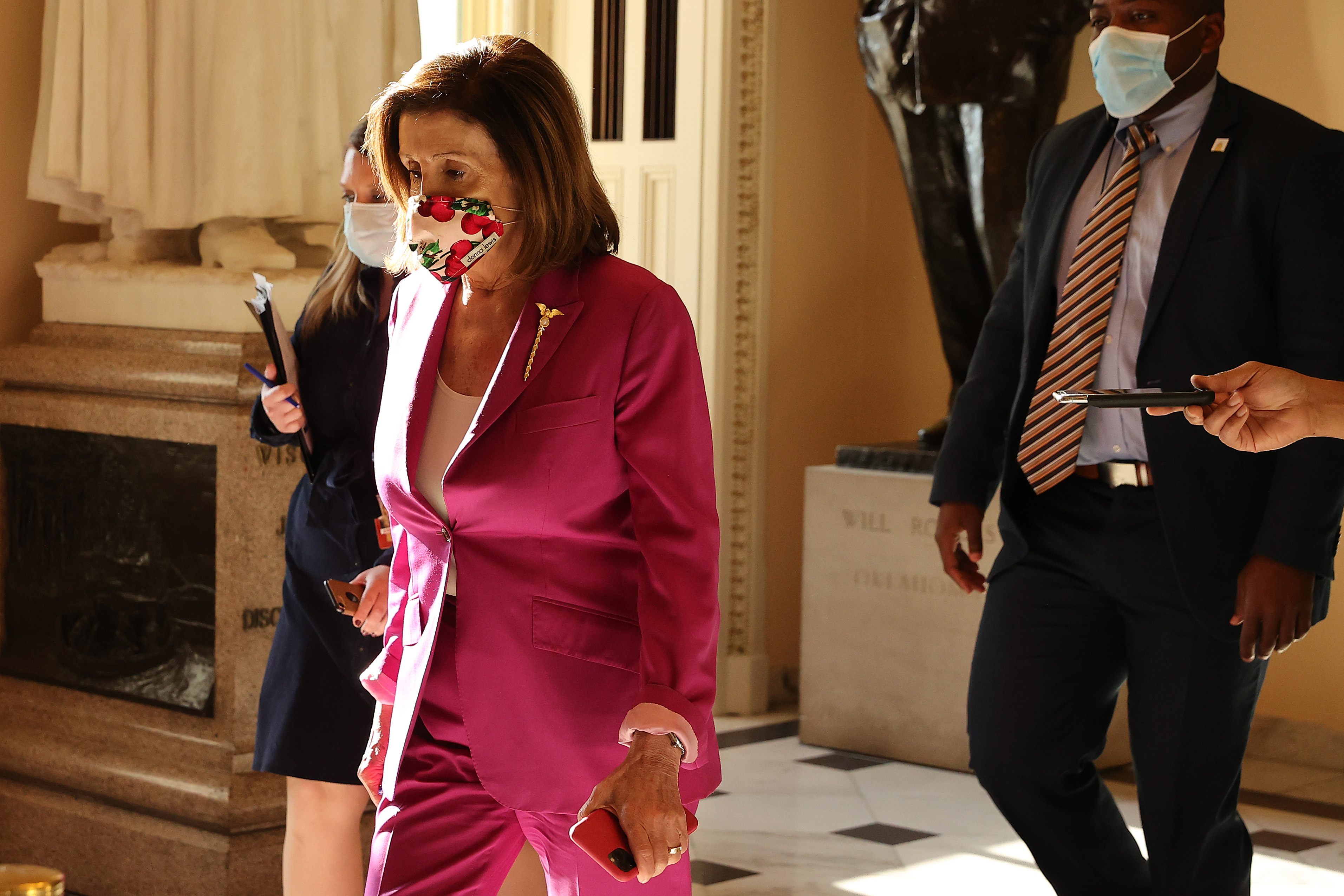 Speaker of the House Nancy Pelosi (D-Calif.) is accompanied by staff, security and press she walks through the U.S. Capitol Friday before a series of votes on a $3 trillion economic package to aid for those affected by the coronavirus pandemic.