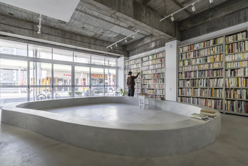 Man browsing bookshelves. A concrete bench takes up much of the room.