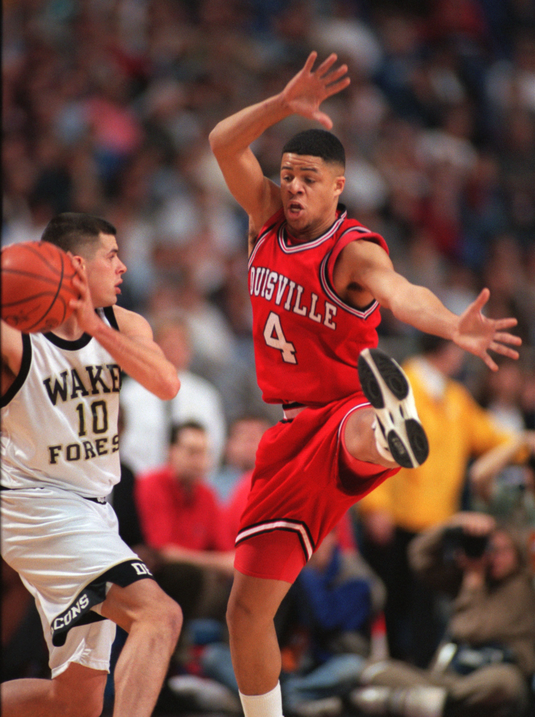 Louisville's Tick Rogers defends against Wake Forest's Rusty LaRue as he was looking for someone to pass to in the first half of their game Thursday night at the Metrodome