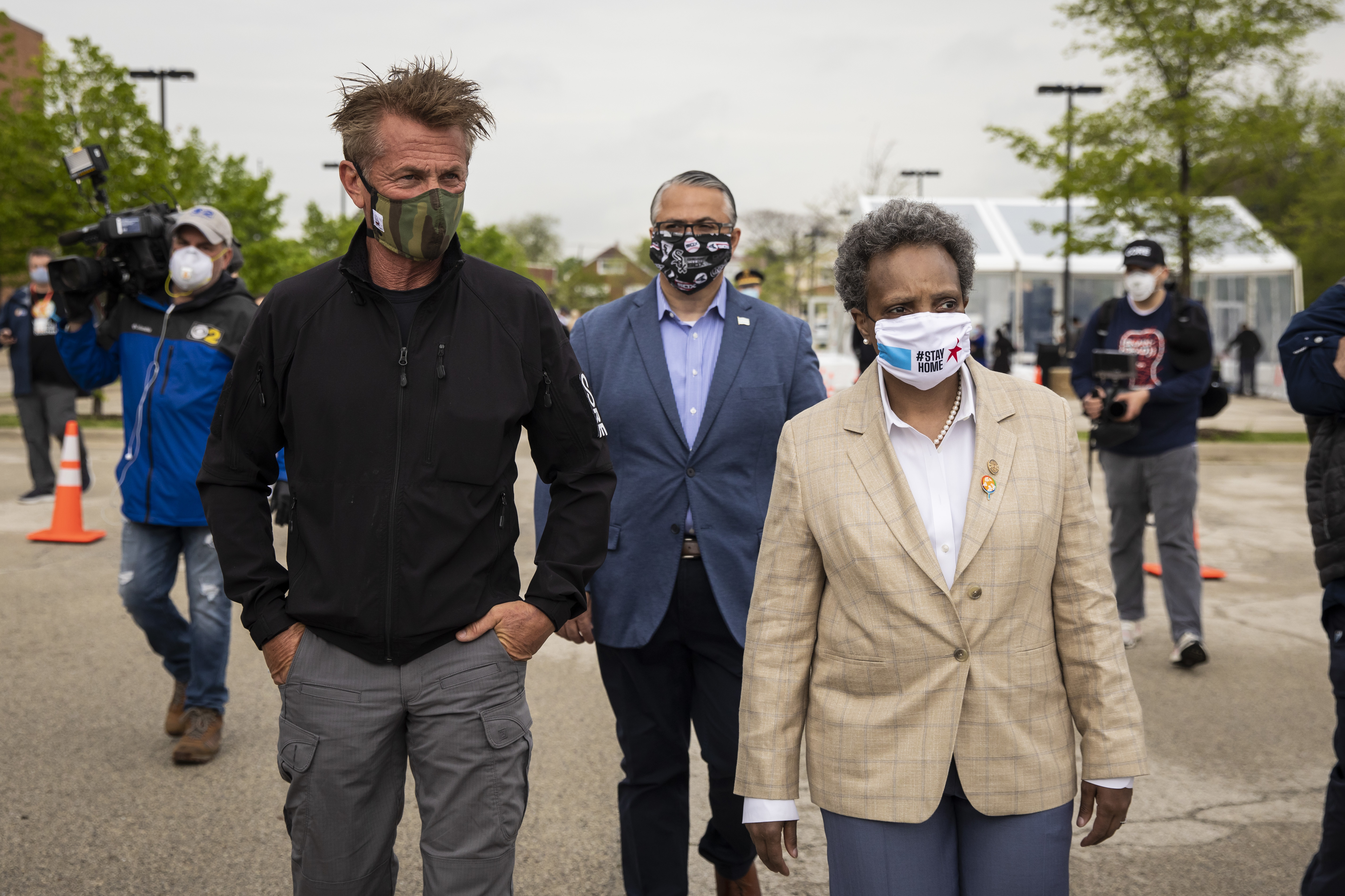 Actor and activist Sean Penn (from left), Ald. Gilbert Villegas (36th) and Mayor Lori Lightfoot tour the new coronavirus drive-thru testing site at Dr. Jorge Prieto Math and Science Academy, 2231 N. Central Ave., on Monday. The CORE disaster relief organization started by Penn is opening that site and five others.