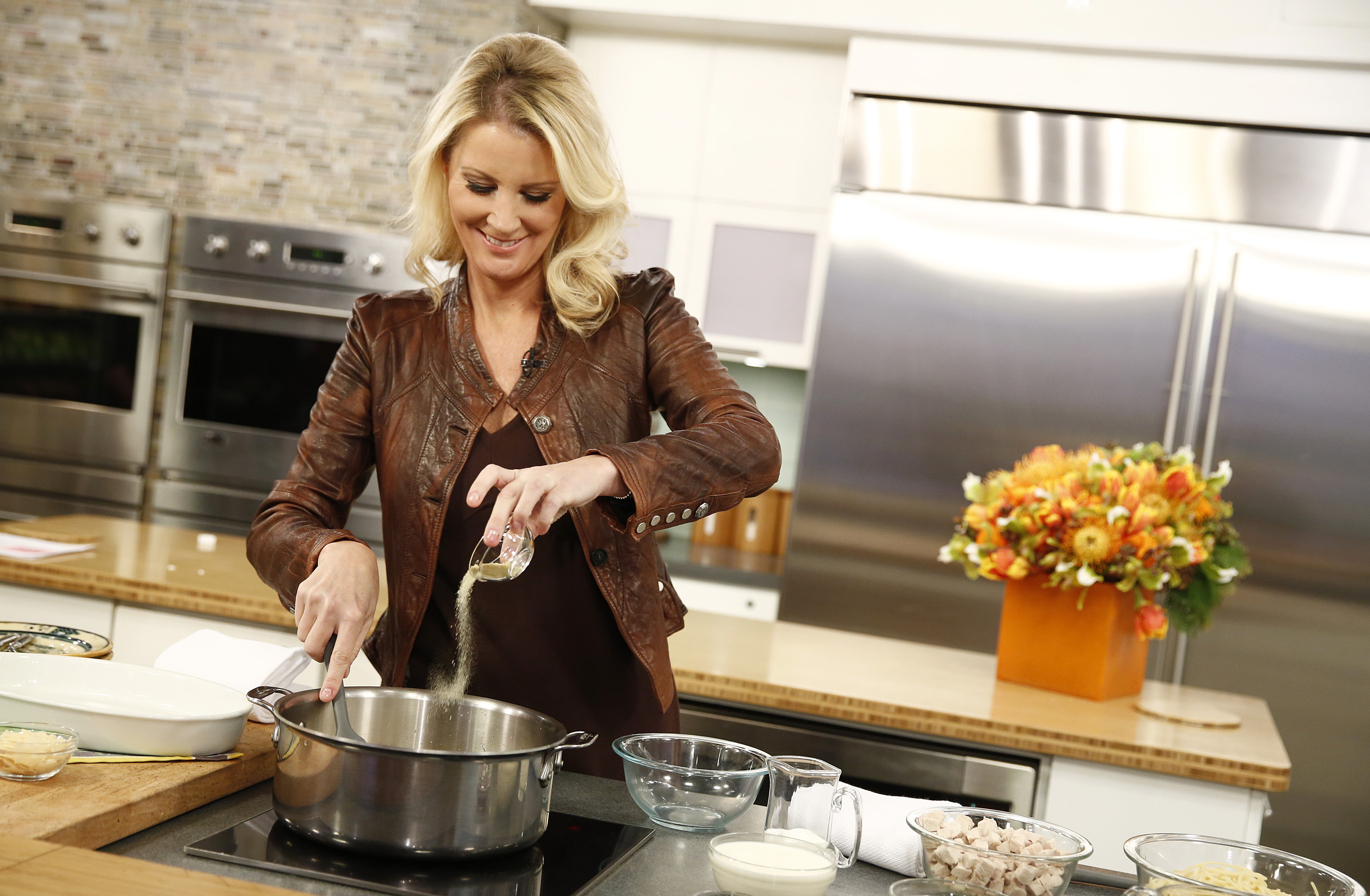 Wearing a brown leather jacket and brown tank top, Sandra Lee cooks using a chrome sautée pan in the Today show's on-set, open kitchen.