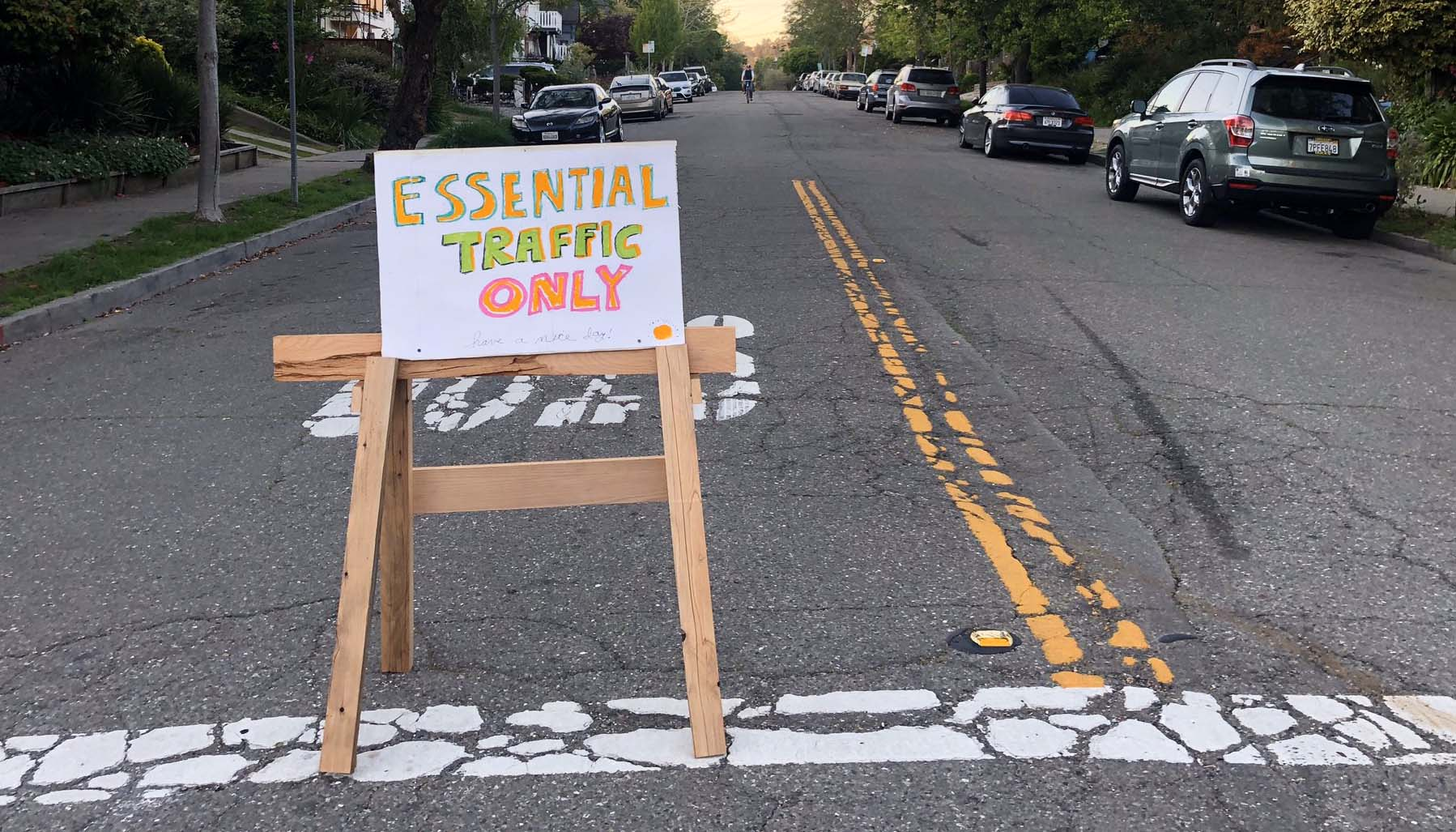 A hand-drawn sign that reads 'essential traffic only' written in neon colors. The sign is propped up on a saw-horse in front of a quiet residential 'slow street,' a street that's been closed in Oakland, California.