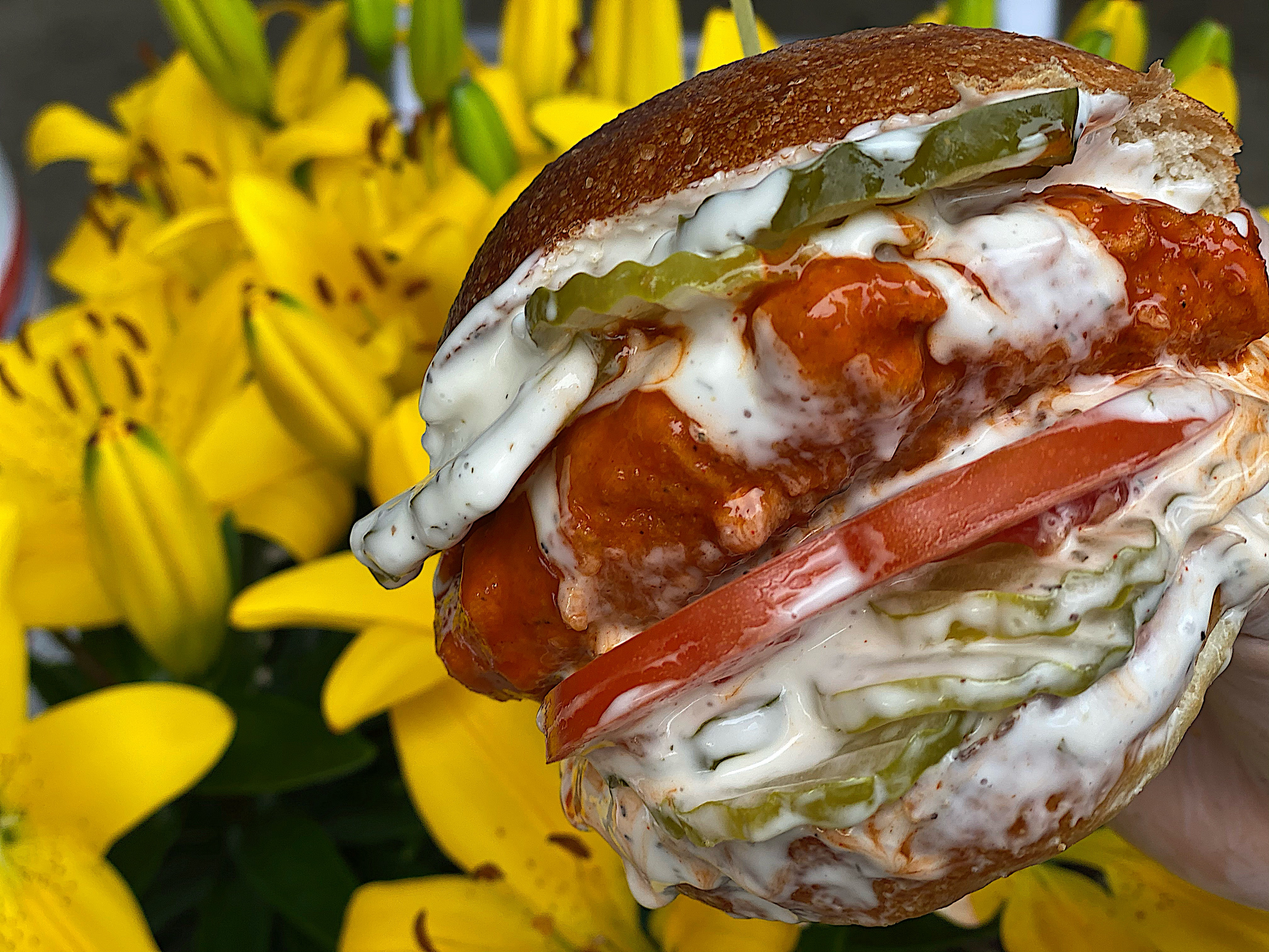A hand holds a vegan, Follow Your Heart bleu-cheese-smothered buffalo chicken sandwich, with tomatoes and pickles peeking out by the chicken. The hand holds the sandwich in front of yellow lilies.