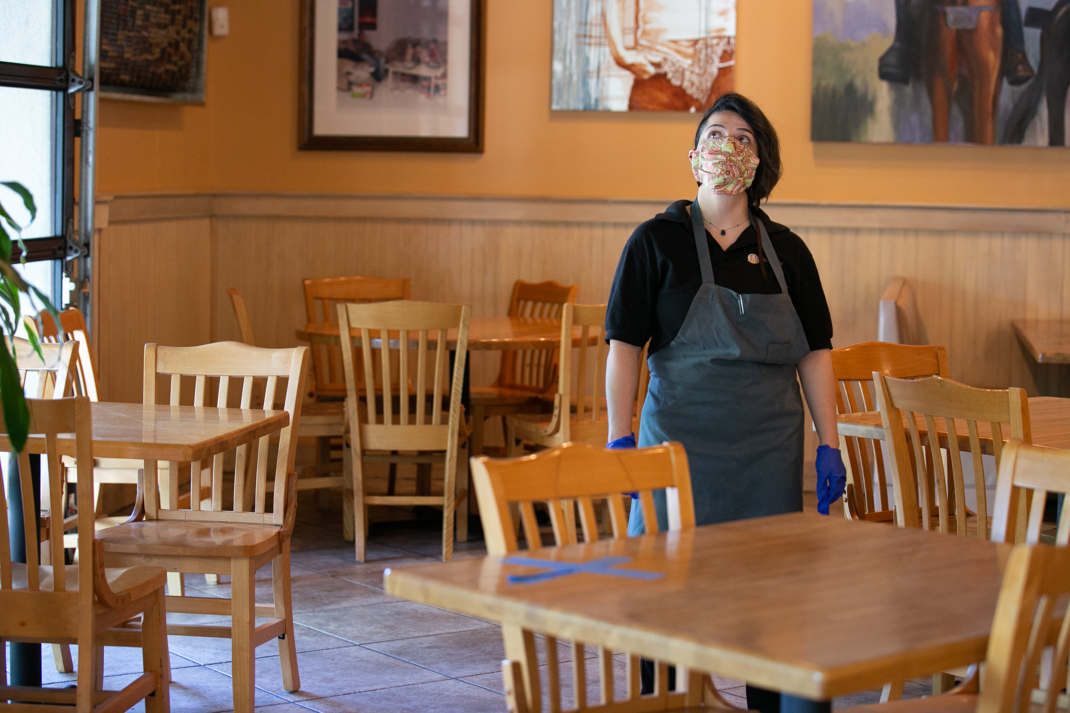 Restaurant worker wearing mask in empty dining room, looks up toward ceiling.