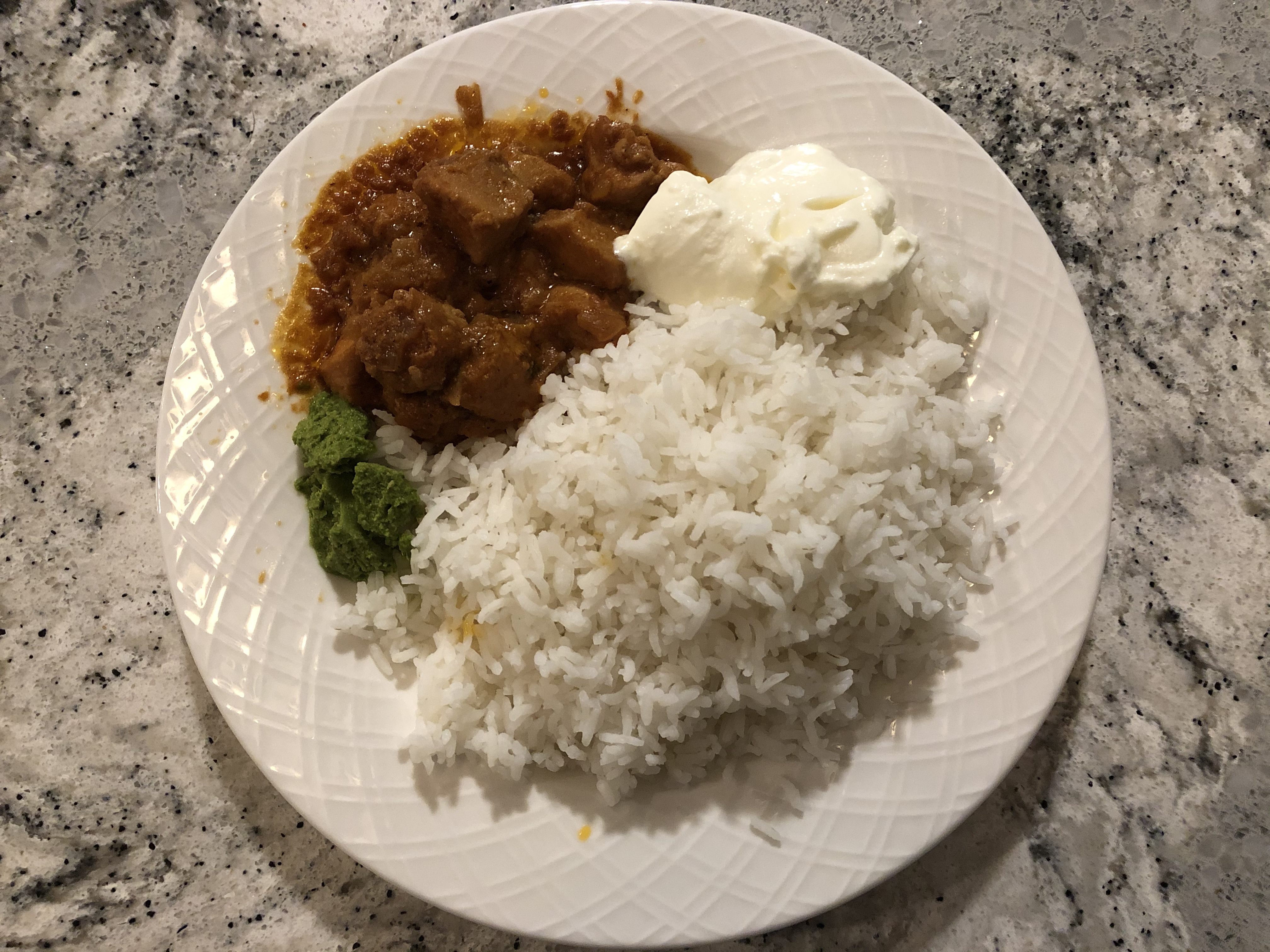Butter chicken made by the author's mother along with white rice, yogurt and the author's mother's cilantro-based chutney.