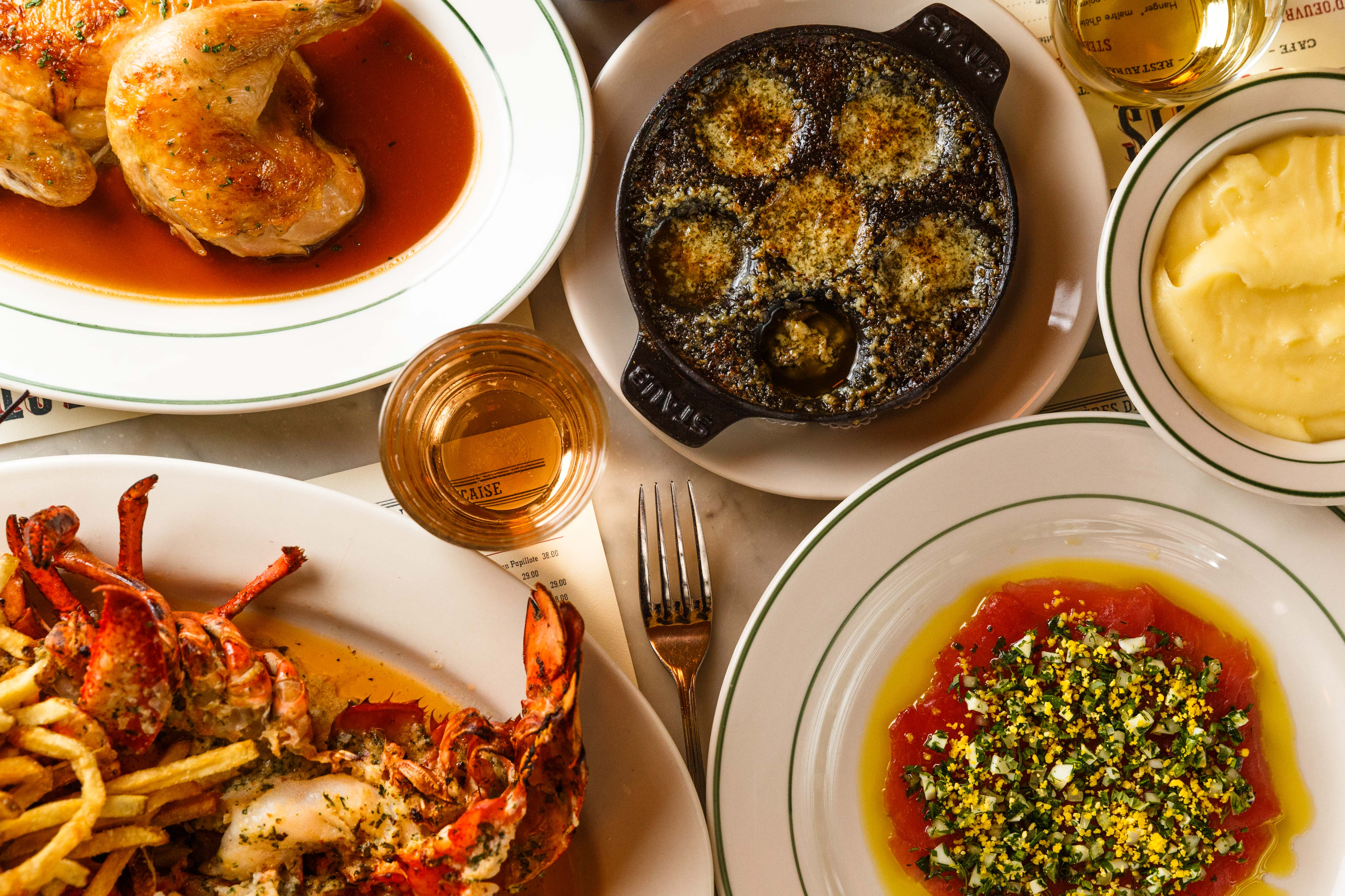 A spread of dishes sit on a table at Pastis, including golden roast chicken, buttered lobster, snails, and crimson raw tuna