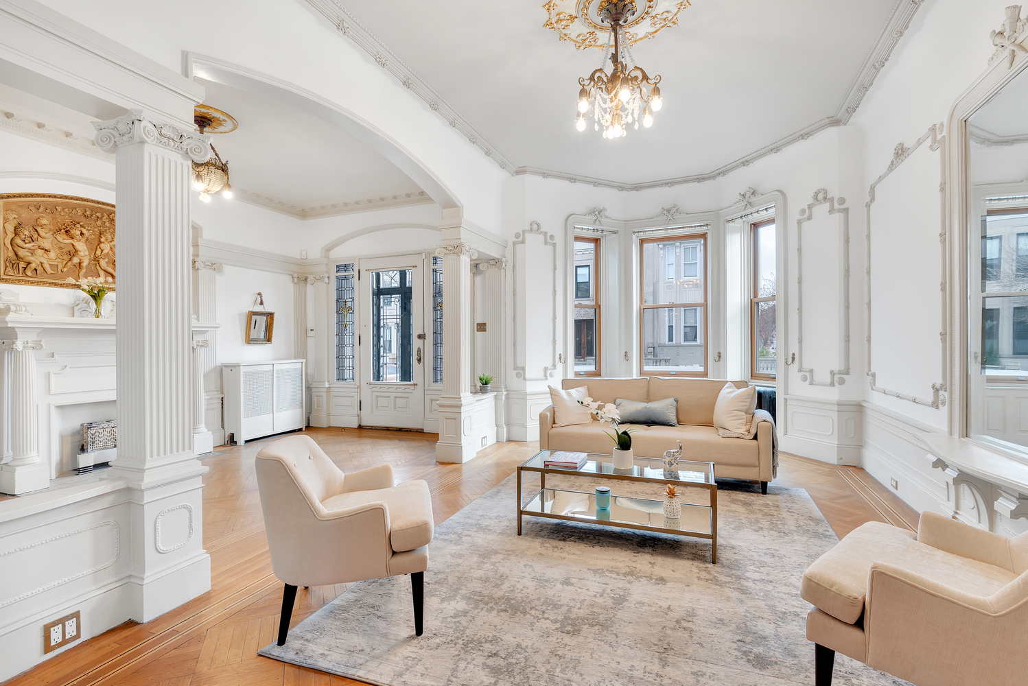 A living area with Ionic columns, hardwood floors, bay windows, and a chandelier.