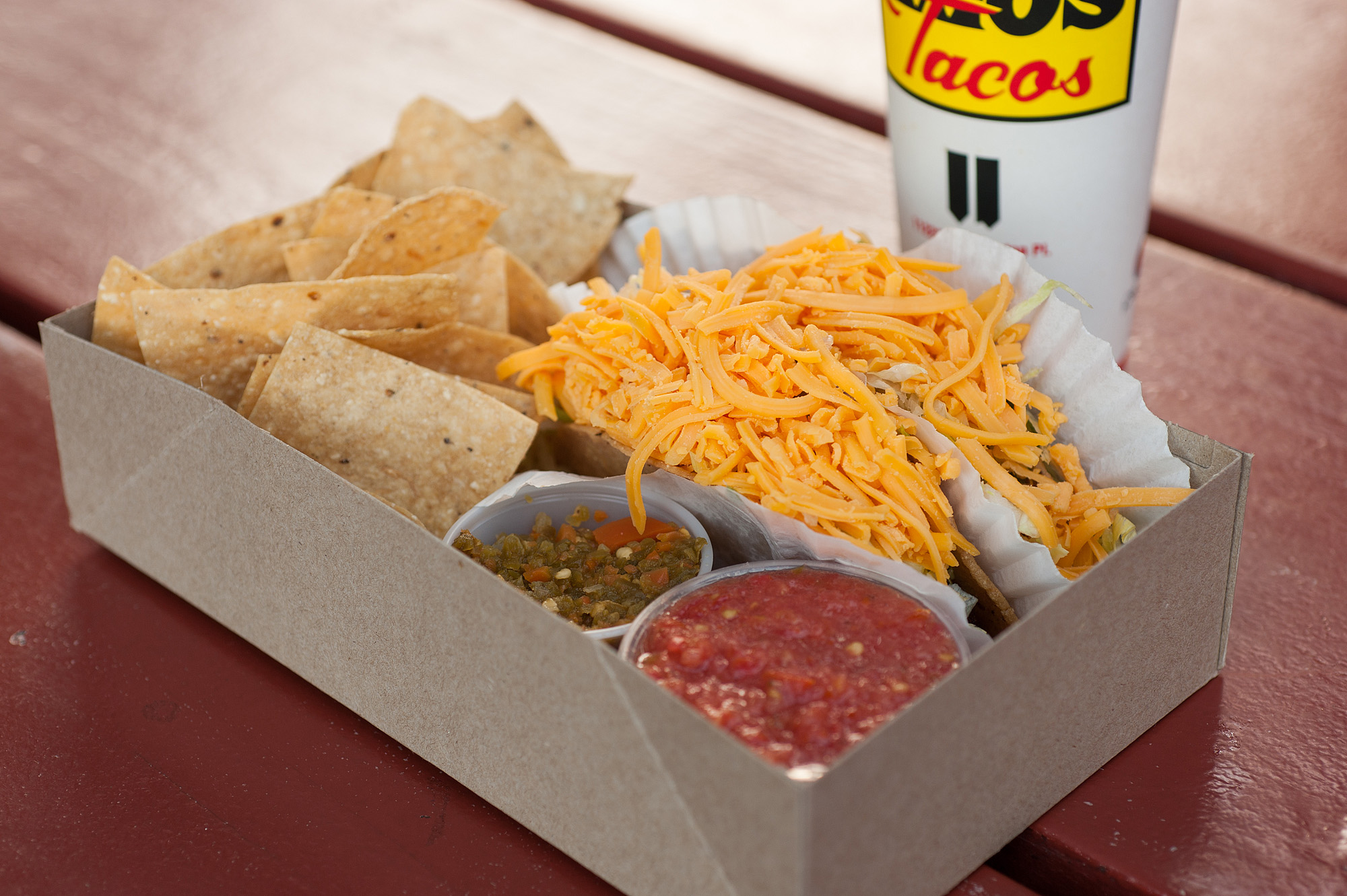 A box of tacos from Tito's, with shredded cheese on top of hard shells.