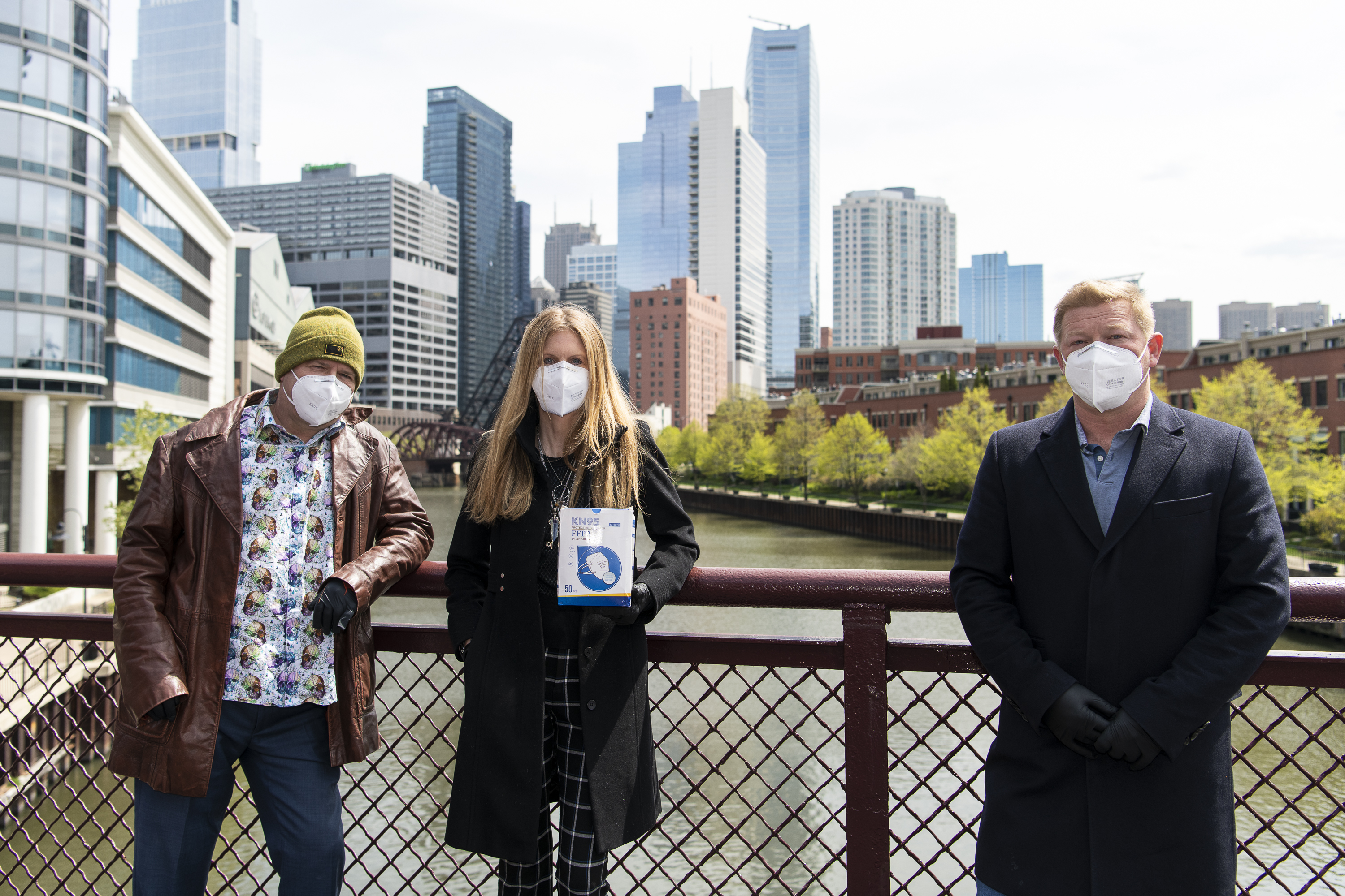John Kucera, left, Kristi Dunn Kucera, center, and Steve Sannikov all with TellUs Global Solutions stand together with a box of N95 masks.